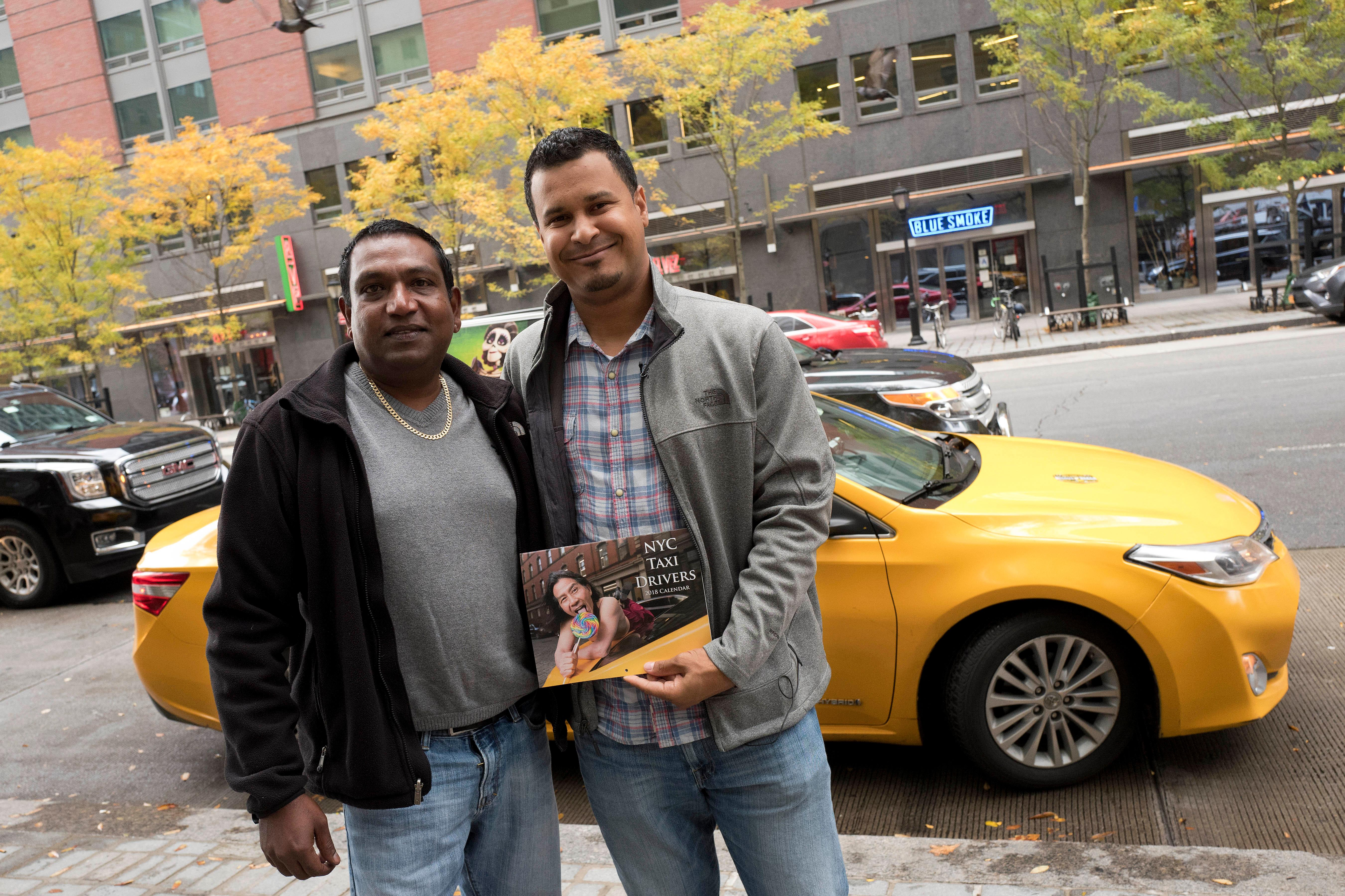 Taxi drivers Terry Samlall, left, and Luis Marte pose for a photo with a copy of the NYC Taxi Drivers calendar, Thursday, Nov. 16, 2017 in New York. Both are featured in the fund-raising calendar. The NYC Taxi Drivers Calendar has twelve New York City cabbies smirking and smoldering their way through 2018 in a tongue-in-cheek pinup calendar that's raising money for a venerable social-service organization.(AP Photo/Mark Lennihan)