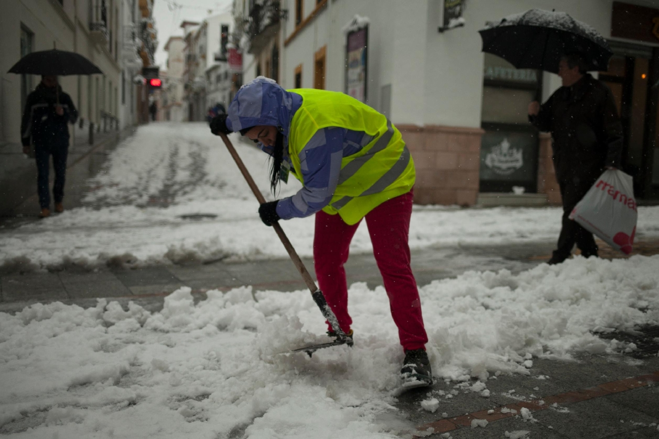 A woman clears snow accumulated on the street after snowfall in the city of Ronda, southern Spain, Thursday, Jan. 19, 2017. (AP Photo/Javier Gonzalez)