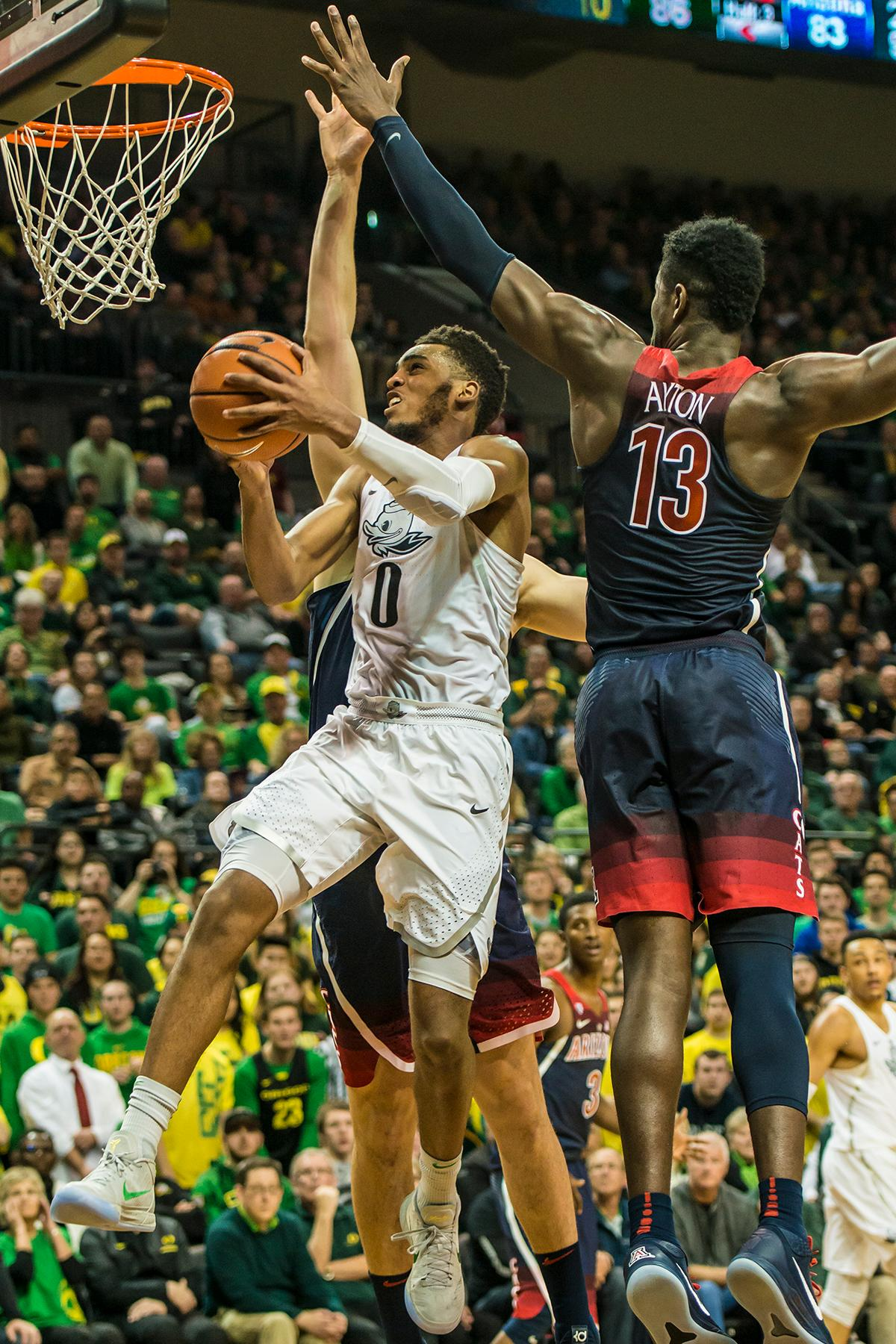 Oregon's Troy Brown jr. (0) goes up against Arizona's DeAndre Ayton in their matchup at Matthew Knight Arena Saturday. The Ducks upset the fourteenth ranked Wildcats 98-93 in a stunning overtime win in front of a packed house of over 12,000 fans for their final home game to improve to a 19-10 (9-7 PAC-12) record on the season. Oregon will finish out regular season play on the road in Washington next week against Washington State on Thursday, then Washington on the following Saturday. (Photo by Colin Houck)