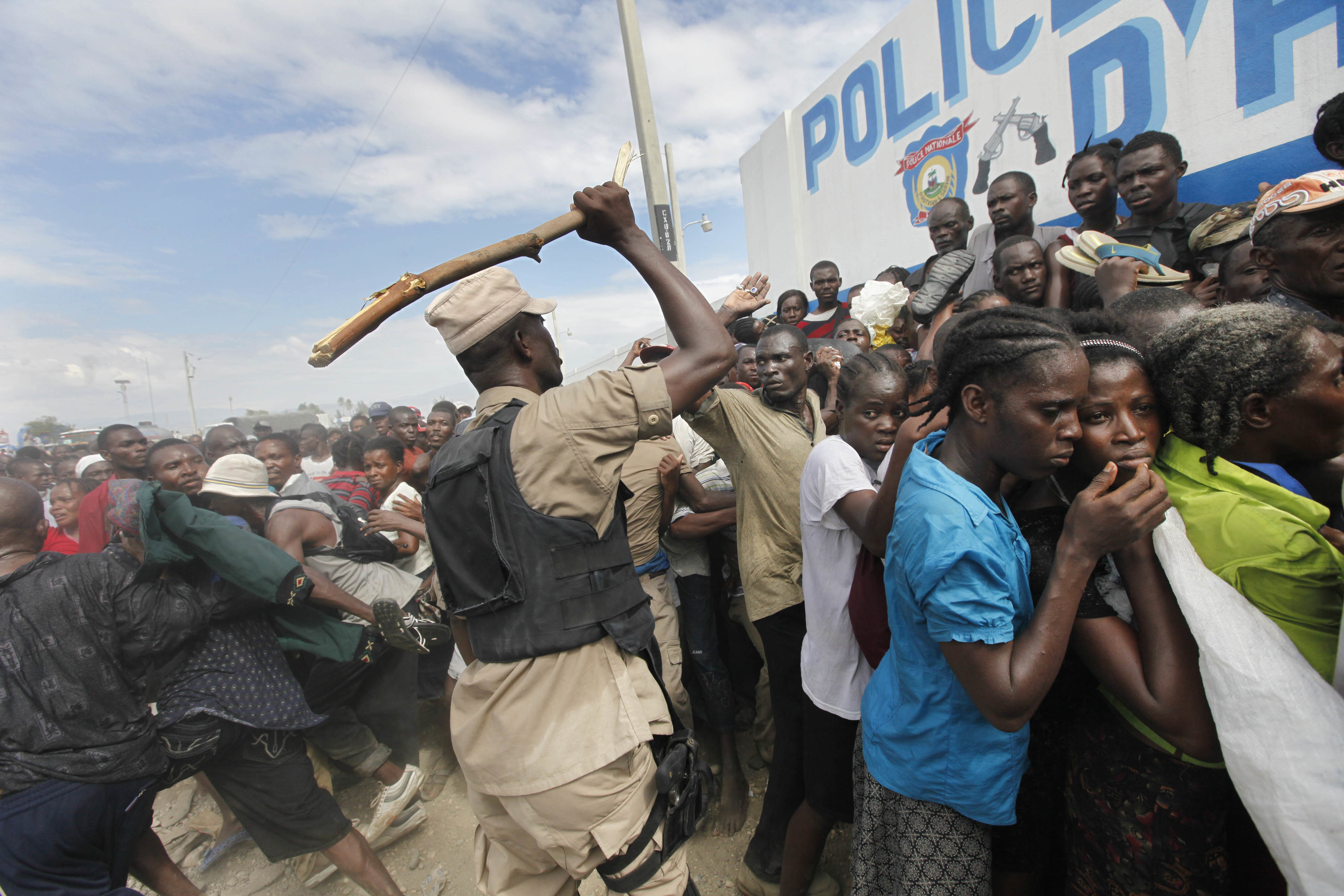 FILE - In this Jan. 26, 2010, file photo, Haitian police use sticks to try and keep the crowd in order at a food distribution point in the Cite Soleil neighborhood in the aftermath of the Jan. 12 earthquake in Port-au-Prince. The Trump administration is hunting for evidence of crimes committed by Haitian immigrants as it decides whether to allow them to continue participating in a humanitarian program that has shielded tens of thousands from deportation since the 2010 earthquake. The Homeland Security Department has not made a final decision about Temporary Protected Status for Haiti and declined to comment on the pre-decisional process. The Obama administration included Haiti in the program shortly after the January 2010 earthquake that killed as many as 300,000 people and devastated schools, hospitals, homes and even entire neighborhoods. (AP Photo/Gerald Herbert, File)