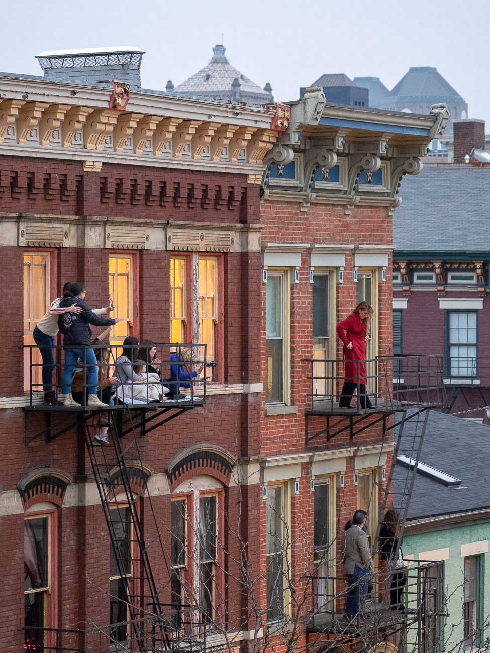 People enjoy the parade from their fire escapes  / Image: Travis Estell // Published: 3.2.19