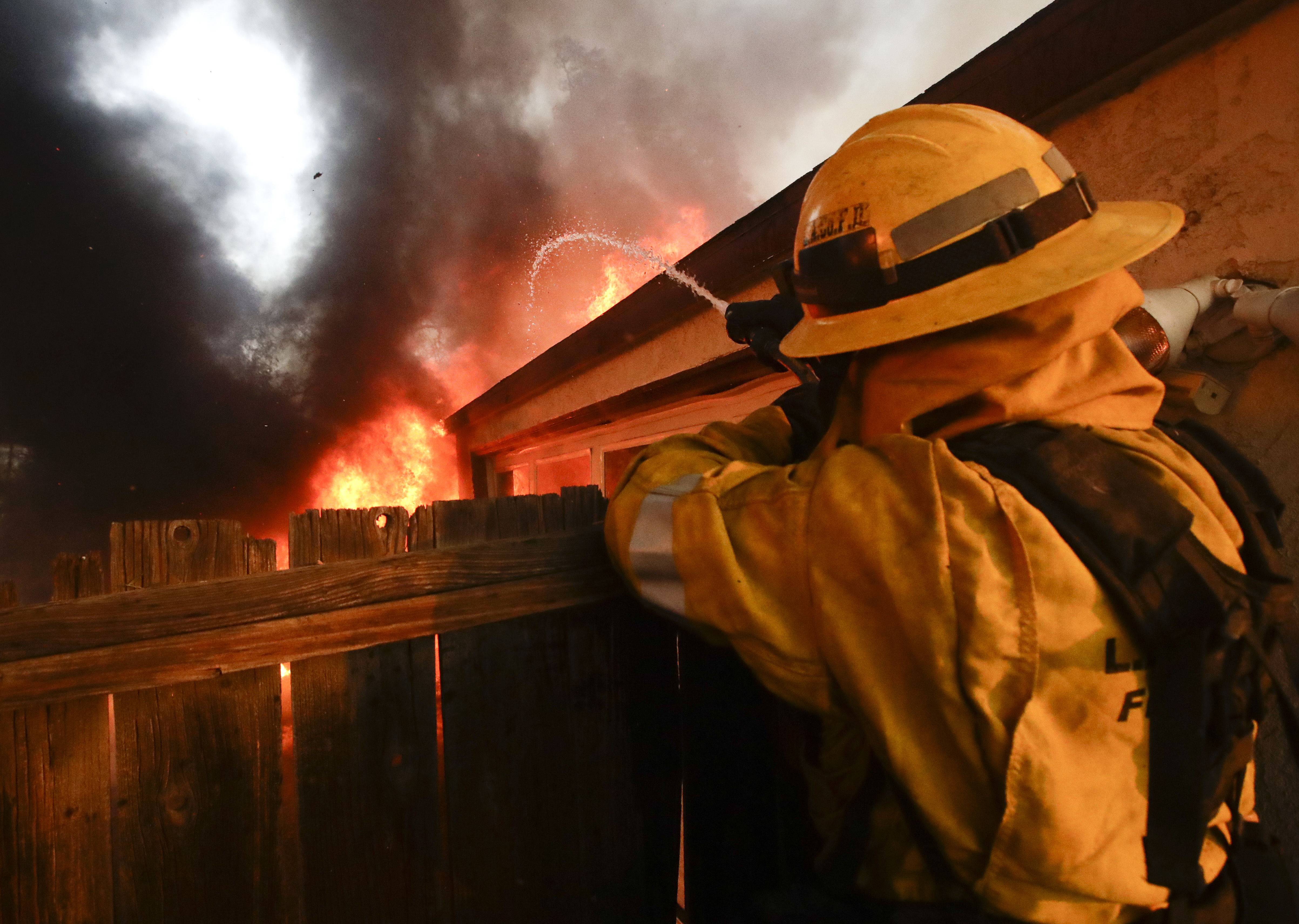 A Los Angeles County firefighter puts water on a burning house during a wildfire in the Lake View Terrace area of Los Angeles Tuesday, Dec. 5, 2017. Ferocious winds in Southern California have whipped up explosive wildfires, burning a psychiatric hospital and scores of other structures. Tens of thousands of people have been ordered evacuated. (AP Photo/Chris Carlson)