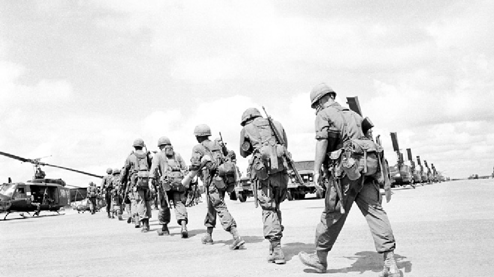 Paratroopers, heavily loaded with their packs, rations for several days and mortar ammunition walk in file across the Bien Hoa airfield, Vietnam on August 11, 1965, to helicopters that will drop them for several days of operation into a jungle clearing in D zone. (AP Photo)
