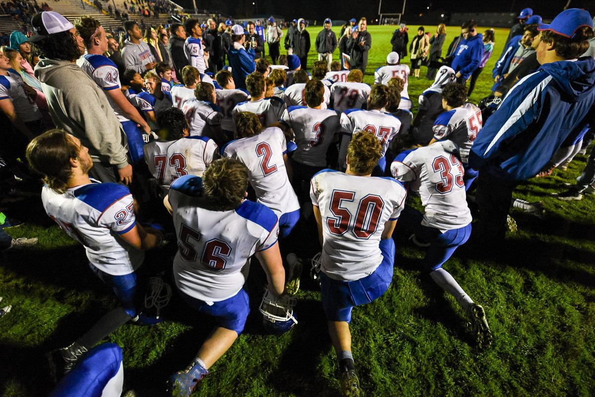 Churchill players take a knee after their 56-7 victory over Springfield, remaining undefeated at 7-0 on the season. Photo by Jeff Dean, Oregon News Lab