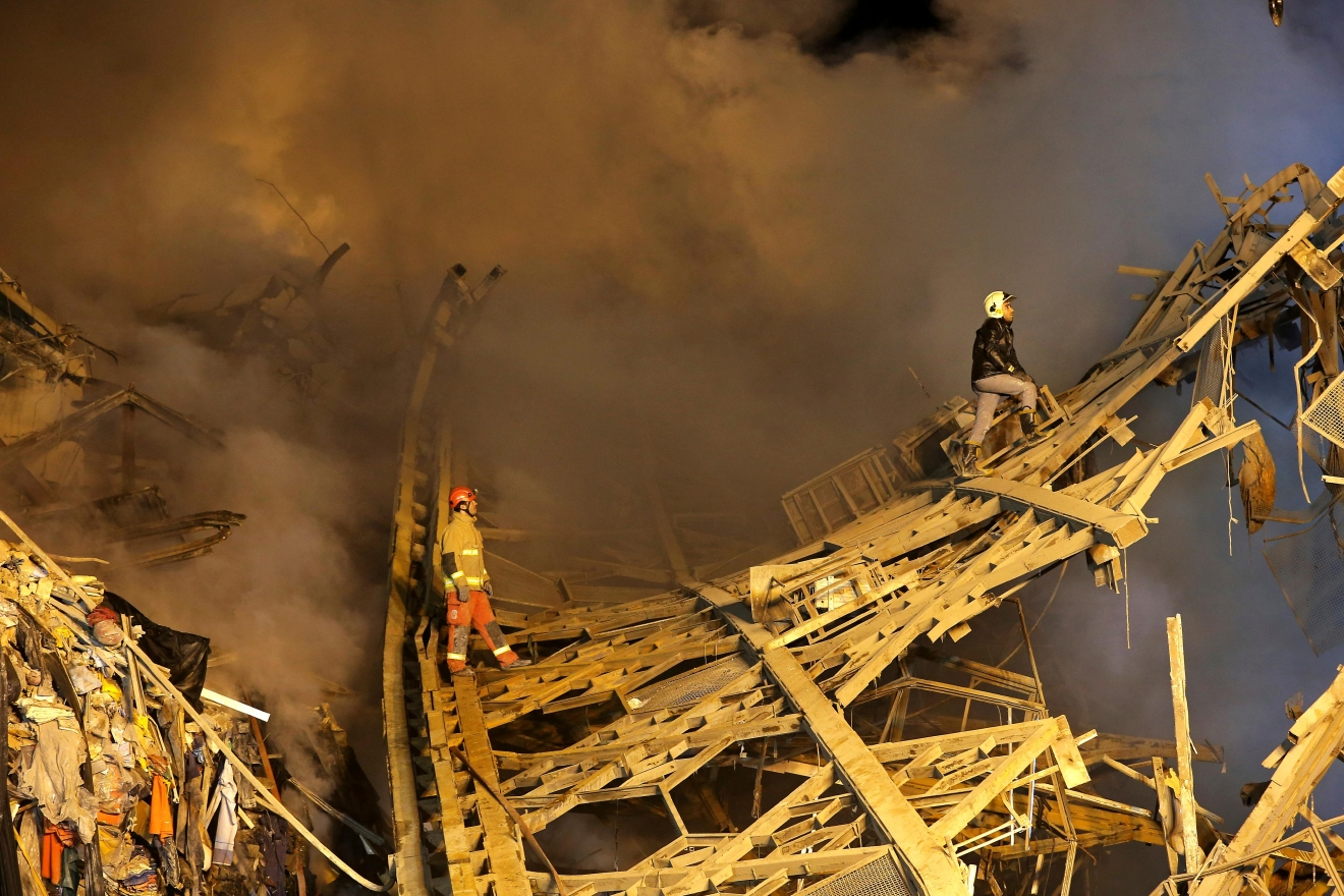 Iranian firefighters work at the scene of the collapsed 17-storey Plasco building after being engulfed by a fire, in central Tehran, Iran, Thursday, Jan. 19, 2017.  Iran's state-run Press TV says dozens of firefighters have been killed in the collapse of a burning high-rise building. (AP Photo/Ebrahim Noroozi)