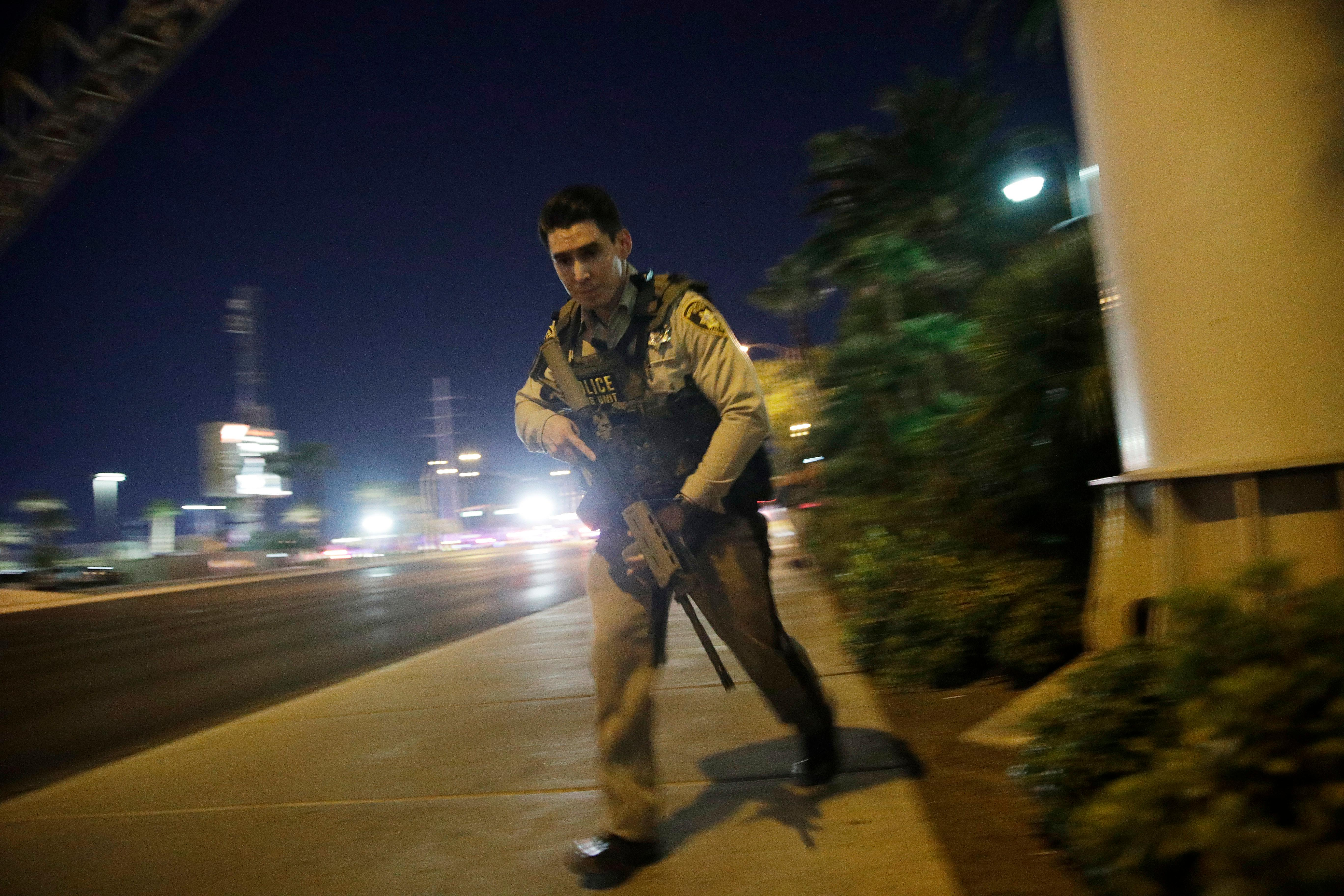 A police officer runs along a sidewalk near a shooting near the Mandalay Bay resort and casino on the Las Vegas Strip, Sunday, Oct. 1, 2017, in Las Vegas. (AP Photo/John Locher)