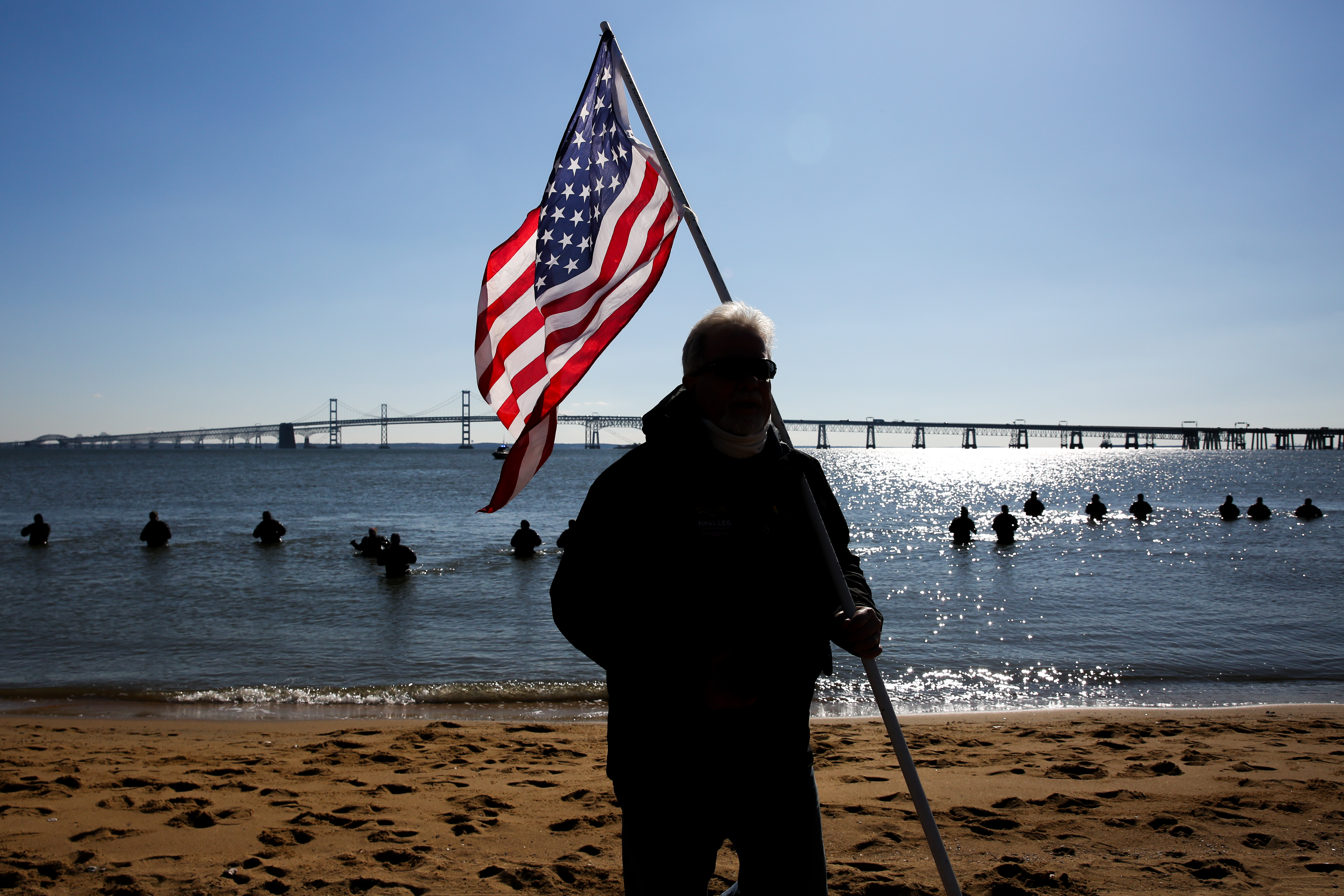 A man holds an American flag in front of the Chesapeake Bay ahead of the Polar Bear Plunge in January.{ }{ }(Amanda Andrade-Rhoades/DC Refined)