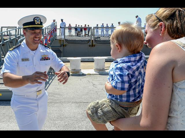 Navy Lt. j.g. Jeremiah Derrick reaches for his son for the traditional first hug upon his return to Naval Station Mayport, Fla., June 4, 2014, following a five-month deployment aboard the USS Halyburton.