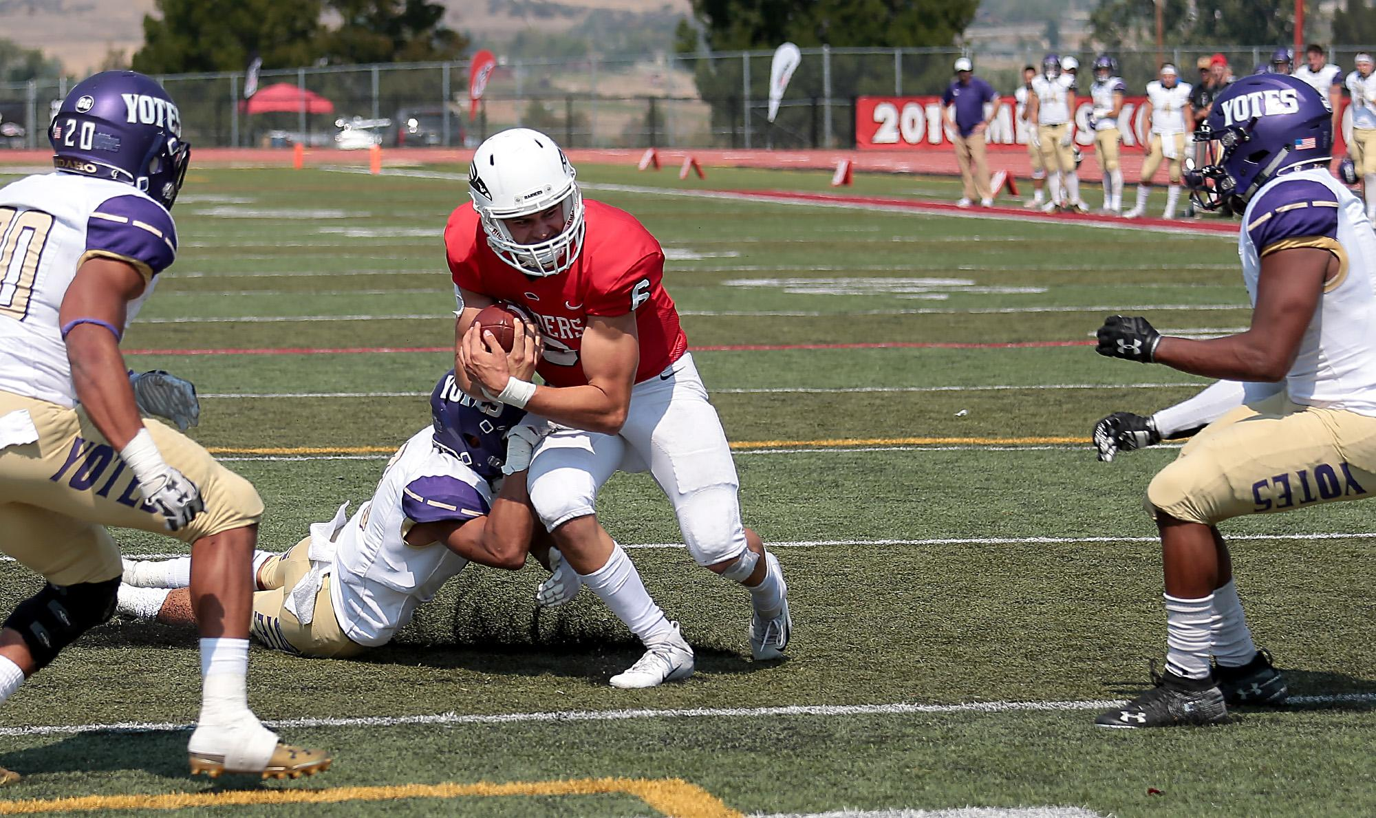 Larry Stauth Jr./For the Daily Tidings<br>Southern Oregon University sophomore quarterback Wyatt Hutchinson fights through College of Idaho defenders and into the end zone for a second-quarter touchdown at Raider Stadium on Saturday.