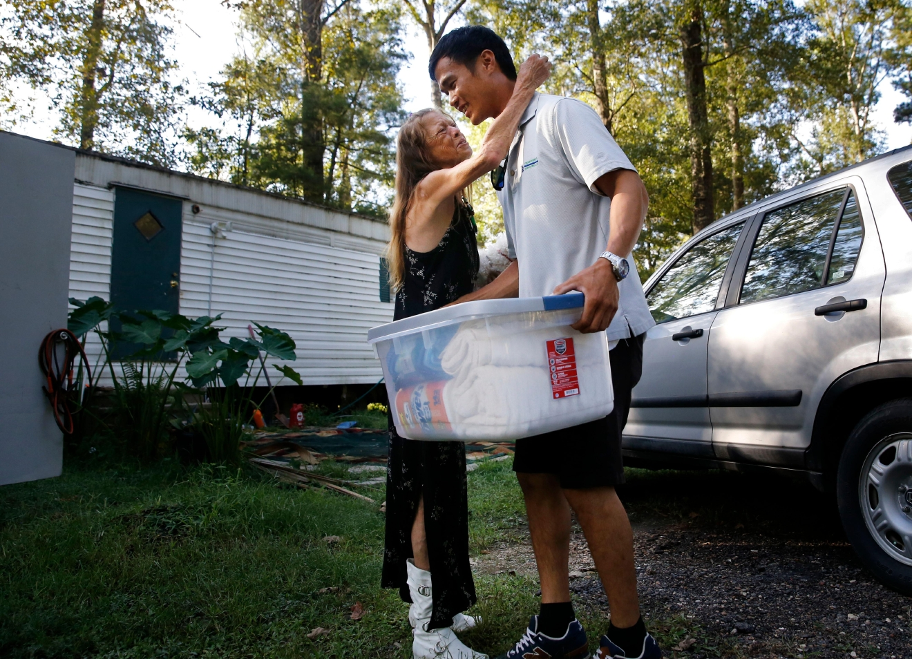 David Phung, who rescued Hailey Brouillette and her dog Sassy from her sinking car in recent floodwaters, hugs her as he gives her a box of household supplies, as they reunite for the first time in Denham Springs, La., Monday, Sept. 12, 2016. An Aug. 13 rescue video shot by WAFB-TV has millions of YouTube views. It shows floodwaters swallowing Brouillette's red convertible as Phung grabbed Brouillette by her arms as the car disappeared in the murky waters. (AP Photo/Gerald Herbert)