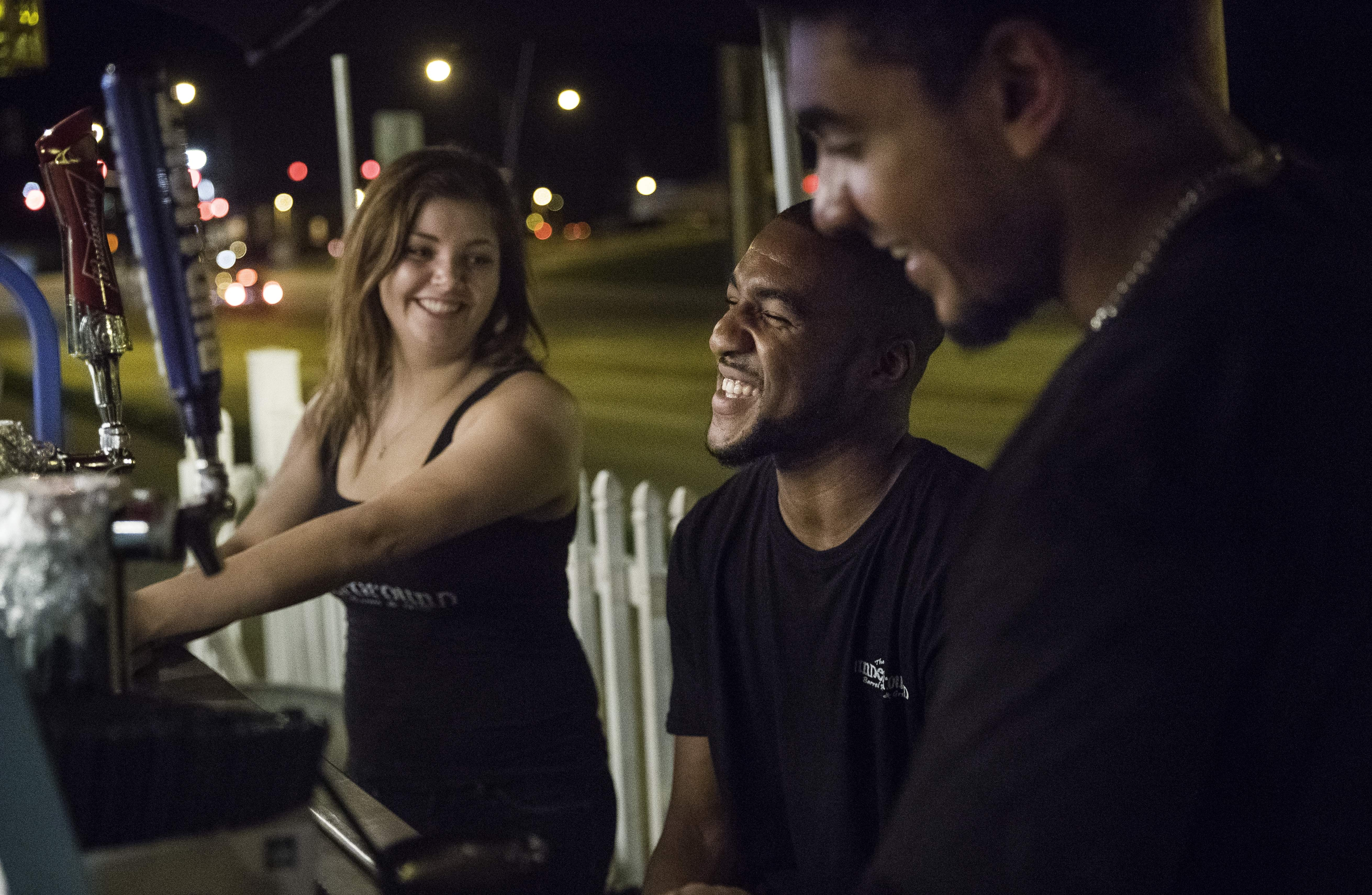 Nicole Mullaney, left, Devon King and Rocky Allen laugh as they pass the time waiting for customers in the beer garden at the Underground Barrel Room & Grill in downtown Carbondale Sunday, Aug. 20, 2017. 'It's not living up to the hype,' Allen said. 'It's been about thirty percent of what I expected.' [Ted Schurter/The State Journal-Register]