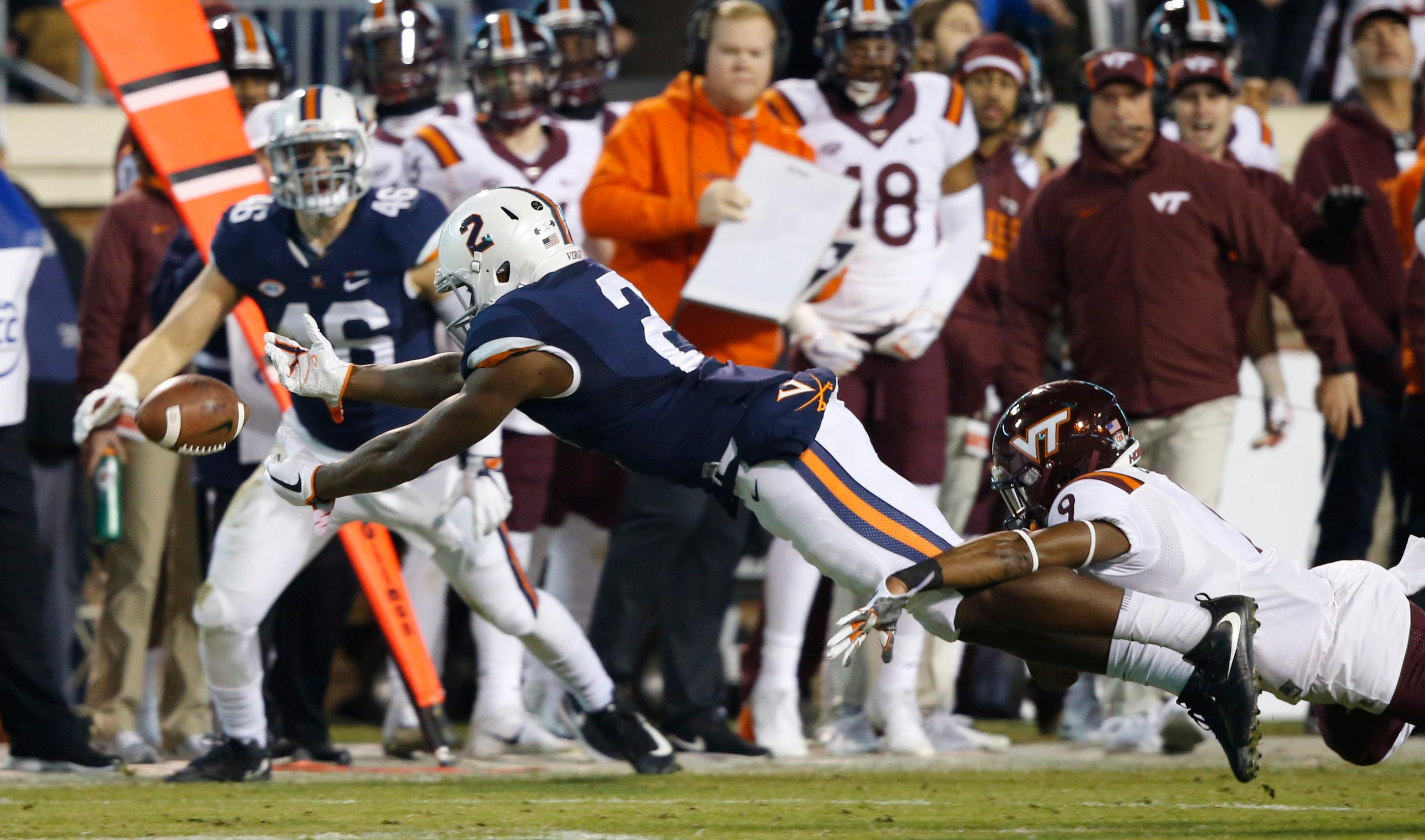Virginia wide receiver Joe Reed (2) stretches out to reach a pass as Virginia Tech defensive back Khalil Ladler (9) defends during the first half of an NCAA college football game in Charlottesville, Va., Friday, Nov. 24, 2017. (AP Photo/Steve Helber)