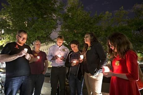 A small group holds a candle light vigil on Freedom Plaza to remember the victims of the shooting at the Washington Navy Yard, Monday, Sept. 16, 2013, in Washington
