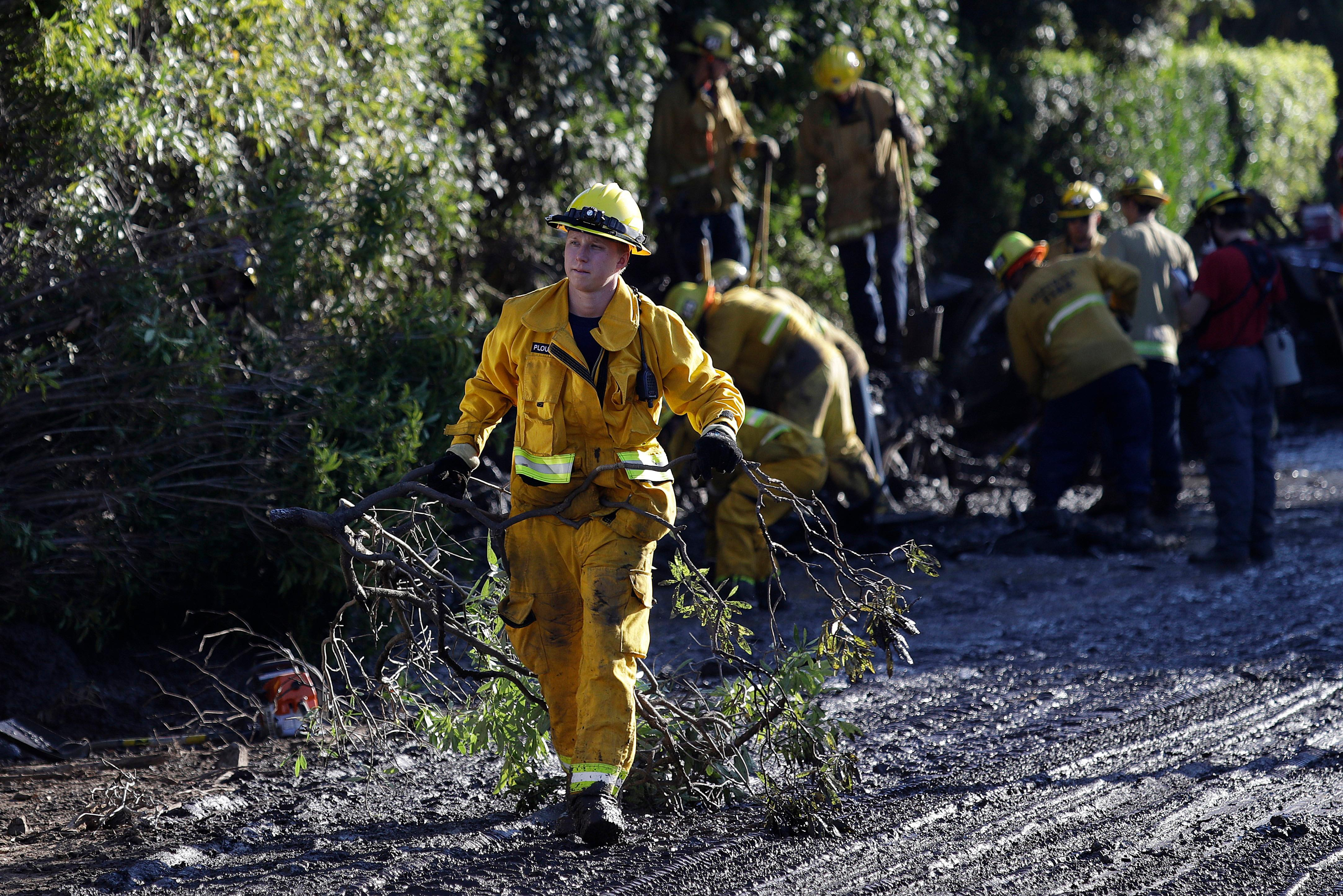 A firefighter cleans debris from an area damaged by storms in Montecito, Calif., Thursday, Jan. 11, 2018. Rescue workers slogged through knee-deep ooze and used long poles to probe for bodies Thursday as the search dragged on for victims of the mudslides that slammed this wealthy coastal town. (AP Photo/Marcio Jose Sanchez)