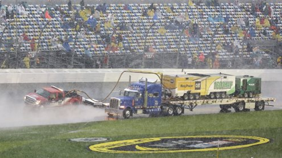 Track dryers go along the front stretch during a rain delay in the Daytona 500 NASCAR Sprint Cup Series auto race at Daytona International Speedway in Daytona Beach, Fla., Sunday, Feb. 23, 2014. (AP Photo/John Raoux)