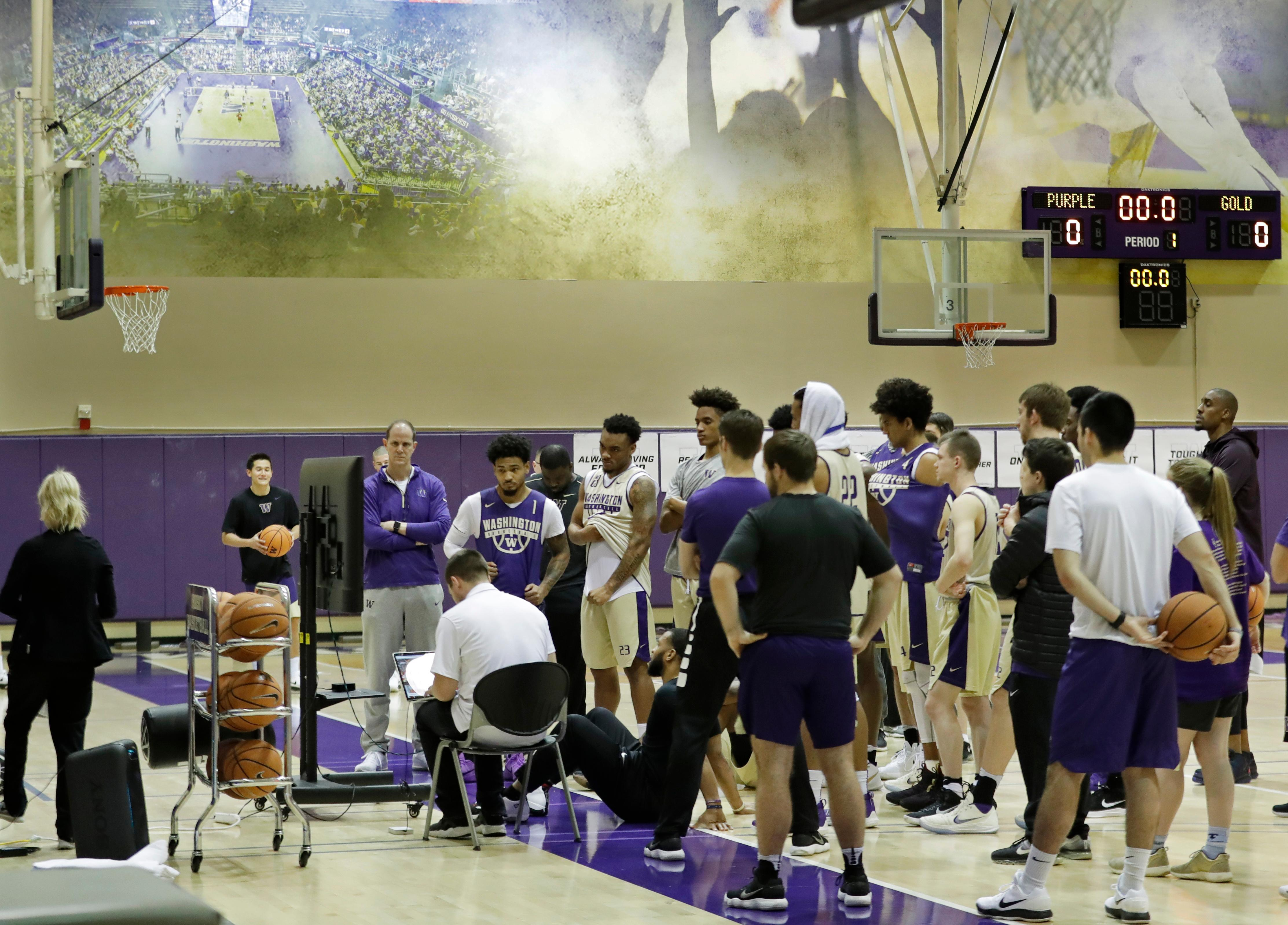 In this Friday, Jan. 26, 2018 photo, Washington head coach Mike Hopkins, third from left, stands near a video monitor during a quick film session at the start of NCAA college basketball practice, two days before Washington's 80-62 win over Washington State in Seattle. One of the most surprising stories in college basketball is what Hopkins is doing in his first season at Washington and how the Huskies are in the conversation for an NCAA bid entering February. (AP Photo/Ted S. Warren)