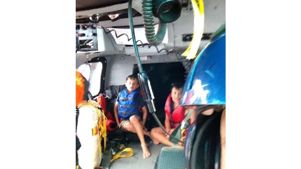 Thomas Alter and Zachary Suri sit on board a Coast Guard Dolphin helicopter from Air Station Traverse City, Mich., after being rescued July 11, 2014. The boys, along with Suri's mother, were rescued from Whaleback Shoal in Green Bay after being stranded on the water overnight when their kayaks went adrift. (U.S. Coast Guard photo courtesy of Cmdr. Shad Soldano)