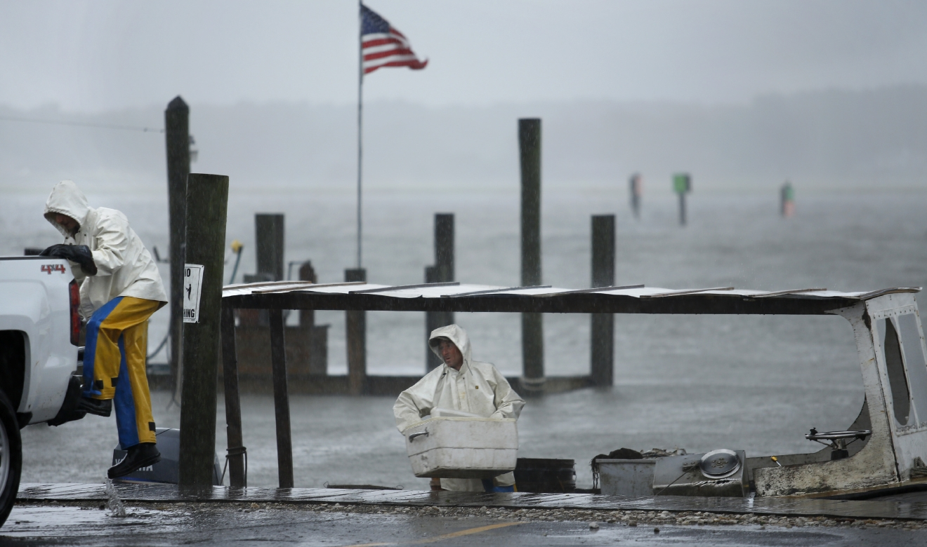 Charlie Gregory, center, a local crabber, and his son Zach check their boat as Tropical Storm Hermine approaches Virginia Beach, Va.,  Saturday, Sept. 3, 2016.  The National Hurricane Center says Tropical Storm Hermine could bring 4 to 7 inches of rain to southeastern Virginia and the Atlantic coastal portion of Maryland as well as 1 to 4 inches of rain over southern Delaware, southern and eastern New Jersey and Long Island through Monday morning.  (Stephen M. Katz/The Virginian-Pilot via AP)