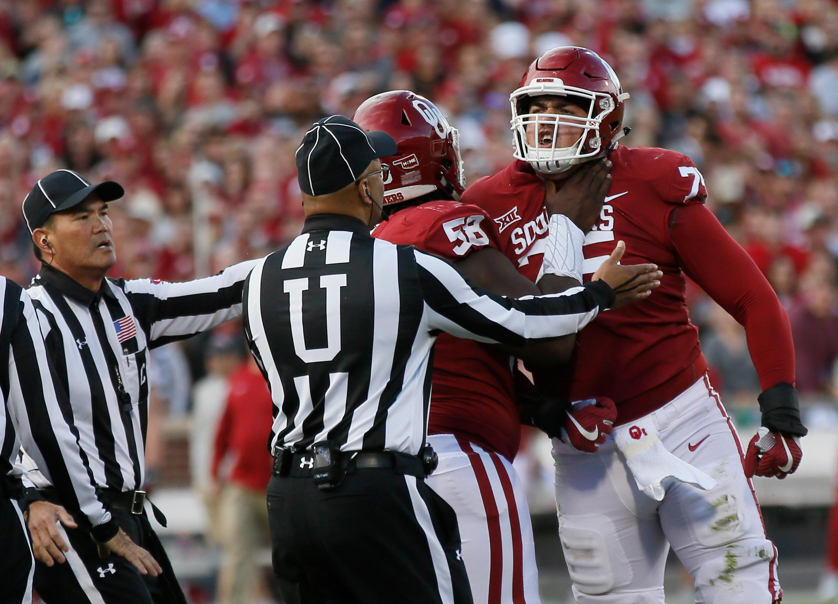 Oklahoma lineman Dru Samia (75) is held back by teammate Erick Wren (58) and officials in the second quarter of an NCAA college football game against West Virginia in Norman, Okla., Saturday, Nov. 25, 2017. Samia received a penalty and was ejected from the game. (AP Photo/Sue Ogrocki)