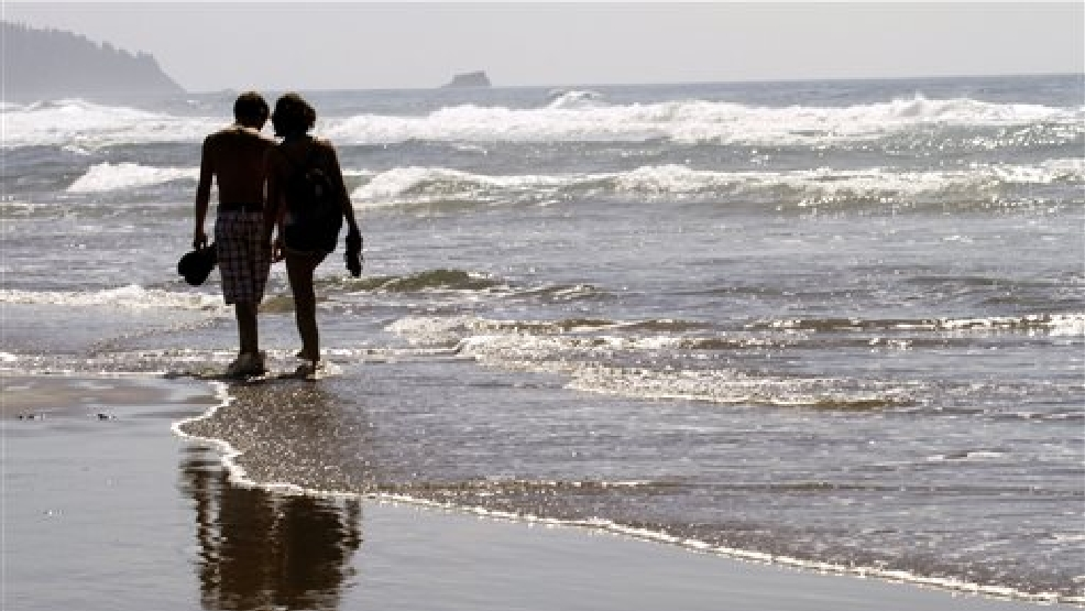 In this Aug. 26, 2010 file photo, a couple walks through the surf together in Cannon Beach, Ore. OKCupid on Monday, July 28, 2014 became the latest company to admit that it has manipulated customer data to see how users of its dating service would react to one another. (AP Photo/Don Ryan, File)