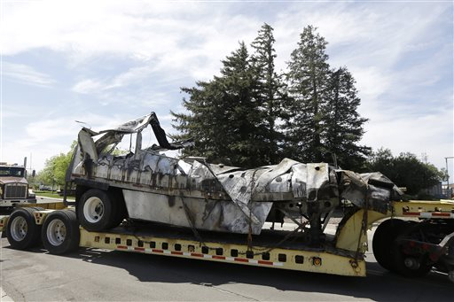 The demolished remains of the FedEx truck involved in the crash are towed into a CalTrans maintenance station in Willows, Calif.