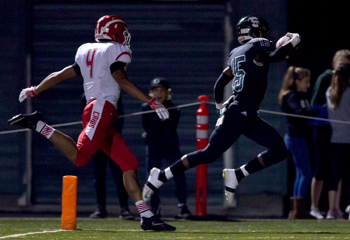 Sheldon wide receiver TC Luvert (#15) leaps into the end zone for a touchdown. The Sheldon Irish defeated the Lincoln Cardinals 38 to 28 to advance to the quarterfinals of the OSAA 6A playoffs. Photo by Ben Lonergan, Oregon News Lab