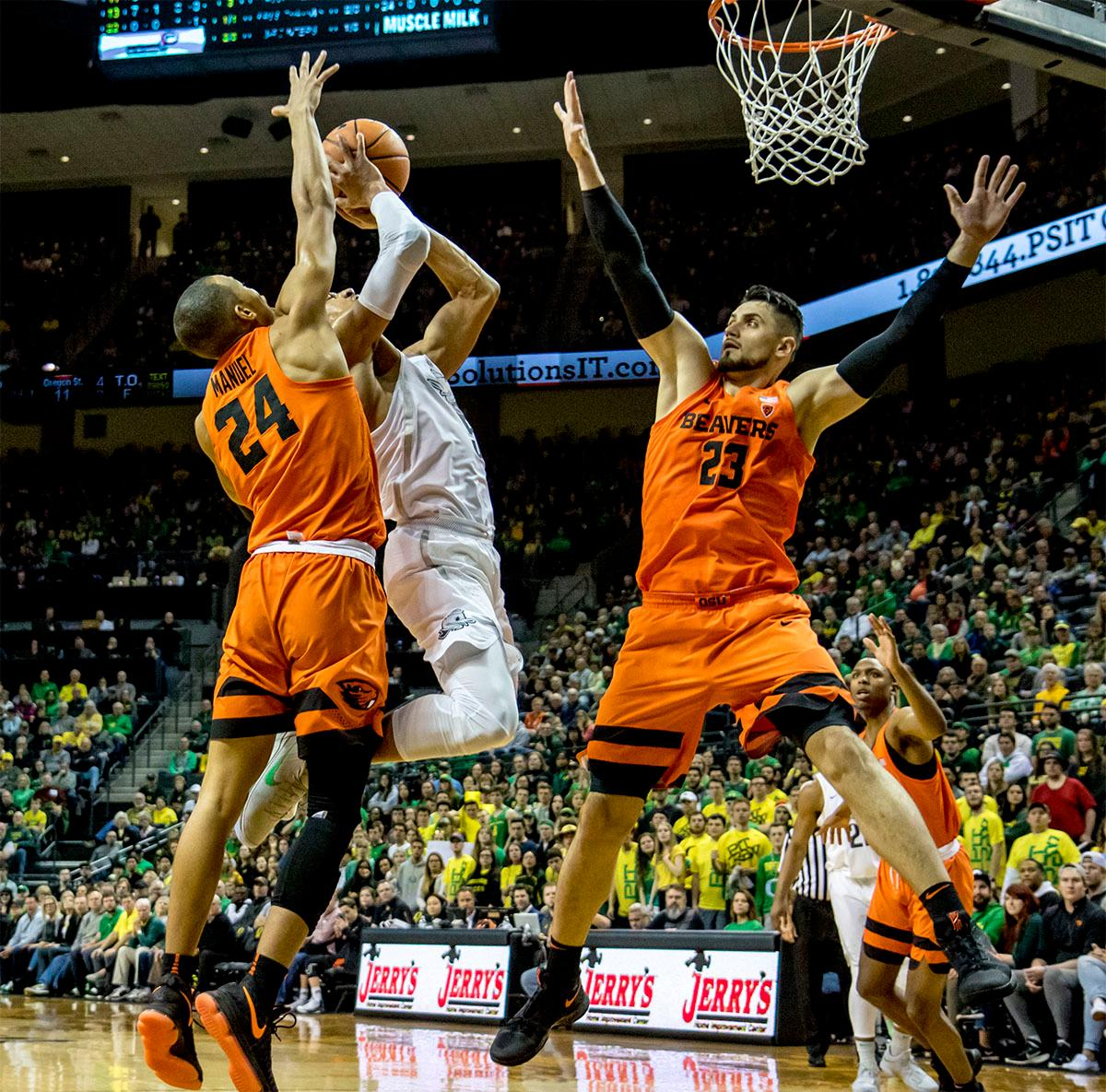 The Duck's Elijah Brown (#5) goes for a jump shot as the Beaver's Gligorije Rakocevic (#23) defends the basket. The Ducks defeated the Beavers in the civil war game, 66-57, at Matthew Knight Arena on Saturday night. Elijah Brown scored a game high of 20 points with 18 of the points coming in the first half, Paul White added 17 points. The Ducks are now 14-7 overall and 4-4 in conference play. The Ducks will next face California on Thursday Feb. 1 at 6:00 p.m. Photo by August Frank, Oregon News Lab