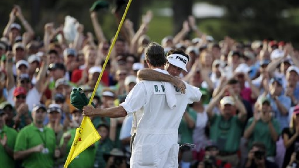 Caddie Ted Scott hugs Bubba Watson after winning the Masters golf tournament Sunday, April 13, 2014, in Augusta, Ga.(AP Photo/Chris Carlson)