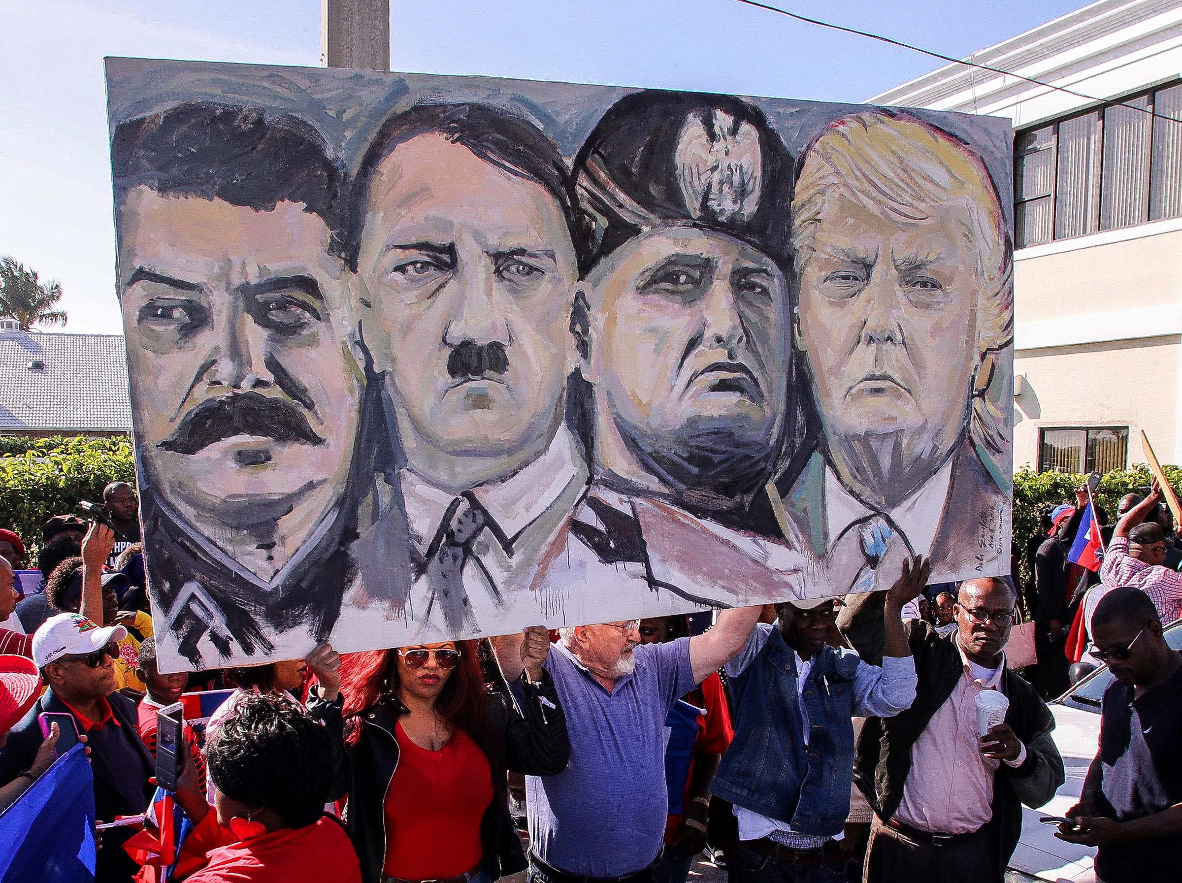 Haitian community members hold an image depicting image shows from left, Joseph Stalin, Adolf Hitler, Benito Mussolini and President Donald Trump during a protest near Trump's Mar-a-Lago estate Monday, Jan. 15, 2018, in West Palm Beach, Fla. Trump is defending himself anew against accusations that he is racist, this time after recent disparaging comments about Haiti and African nations. The group said they were there to demand an apology from the Trump. (Damon Higgins/Palm Beach Post via AP)