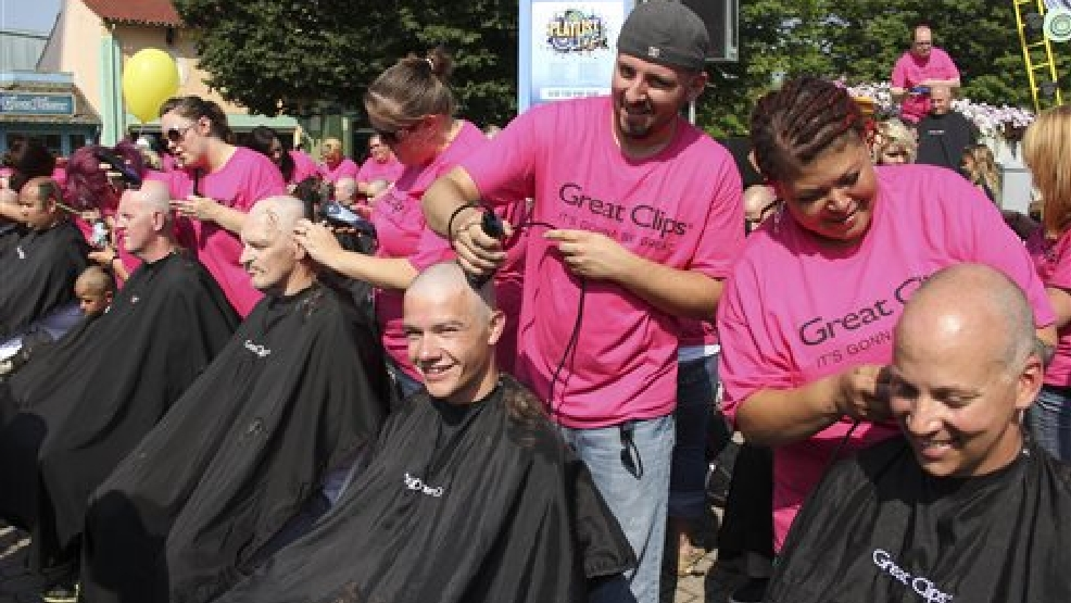 Hair stylists from 26 Great Clips Ohio salons shave the heads of over 200 people, Friday, Aug. 1, 2014, at Kings Island amusement park in Mason, Ohio, in an attempt to set a new Guinness world record and to raise awareness and money to fight cancer. Kings Island says 213 heads were shaved and the current record is 182. A Guinness spokeswoman says it will take about six to eight weeks to process the park's claim on the record. (AP Photo/Courtesy of Kings Island, Don Helbig)