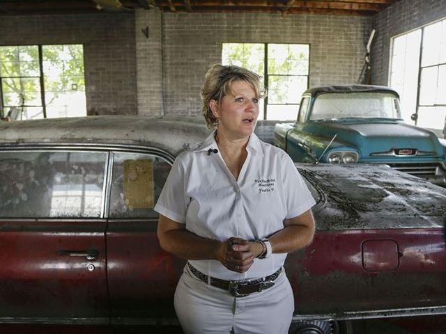 Auctioneer Yvette VanDerBrink stands in front of a new 1963 Chevrolet Impala and new 1958 Cameo pickup truck at the former Lambrecht Chevrolet car dealership.