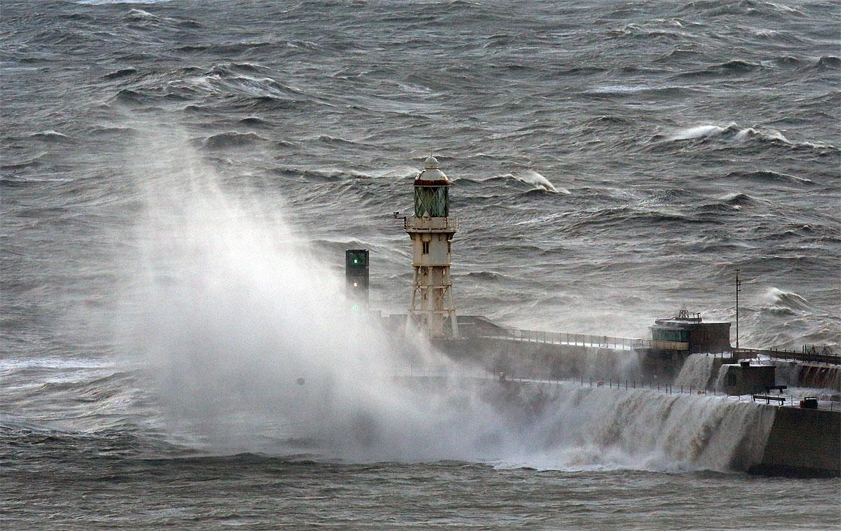 Waves crash over the harbour wall in Dover, south east England, as a storm, Storm Angus, the year's first big winter storm in Britain, lashes England's south coast, Sunday Nov. 20, 2016. Forecasters say winds of 68 mph (110 kph) hit the south coast early Sunday, with a gust of 97 mph (156 kph) recorded offshore. (Gareth Fuller/PA via AP)