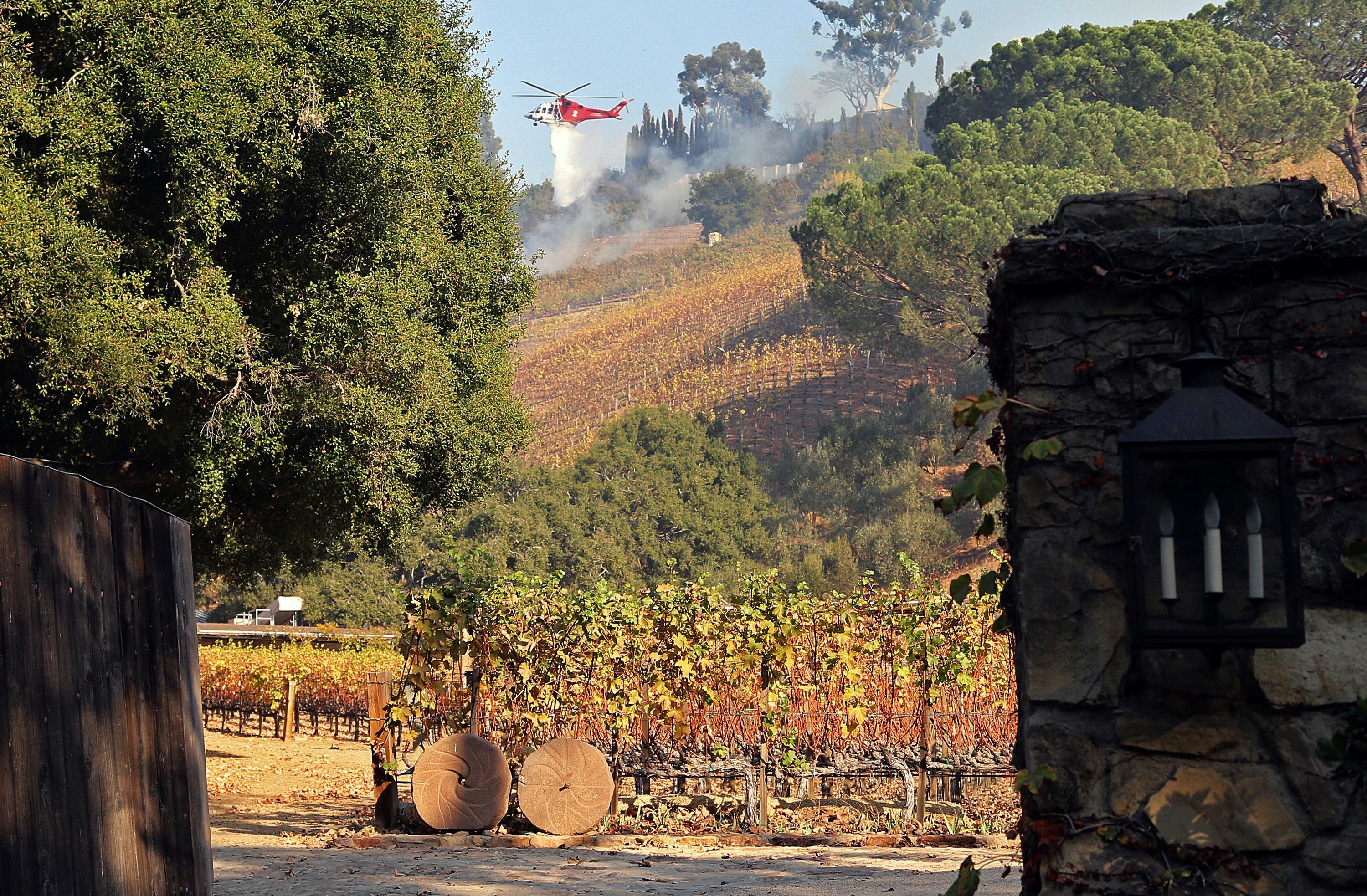 In this Wednesday, Dec. 6, 2017 photo, a Los Angeles Fire Department helicopter makes a water drop on media mogul Rupert Murdoch's 16-acre (6.5-hectare) Moraga Vineyards estate, where about 7 acres (2.8 hectares) of vines appeared to have been damaged, a spokeswoman said.  (AP Photo/Reed Saxon)
