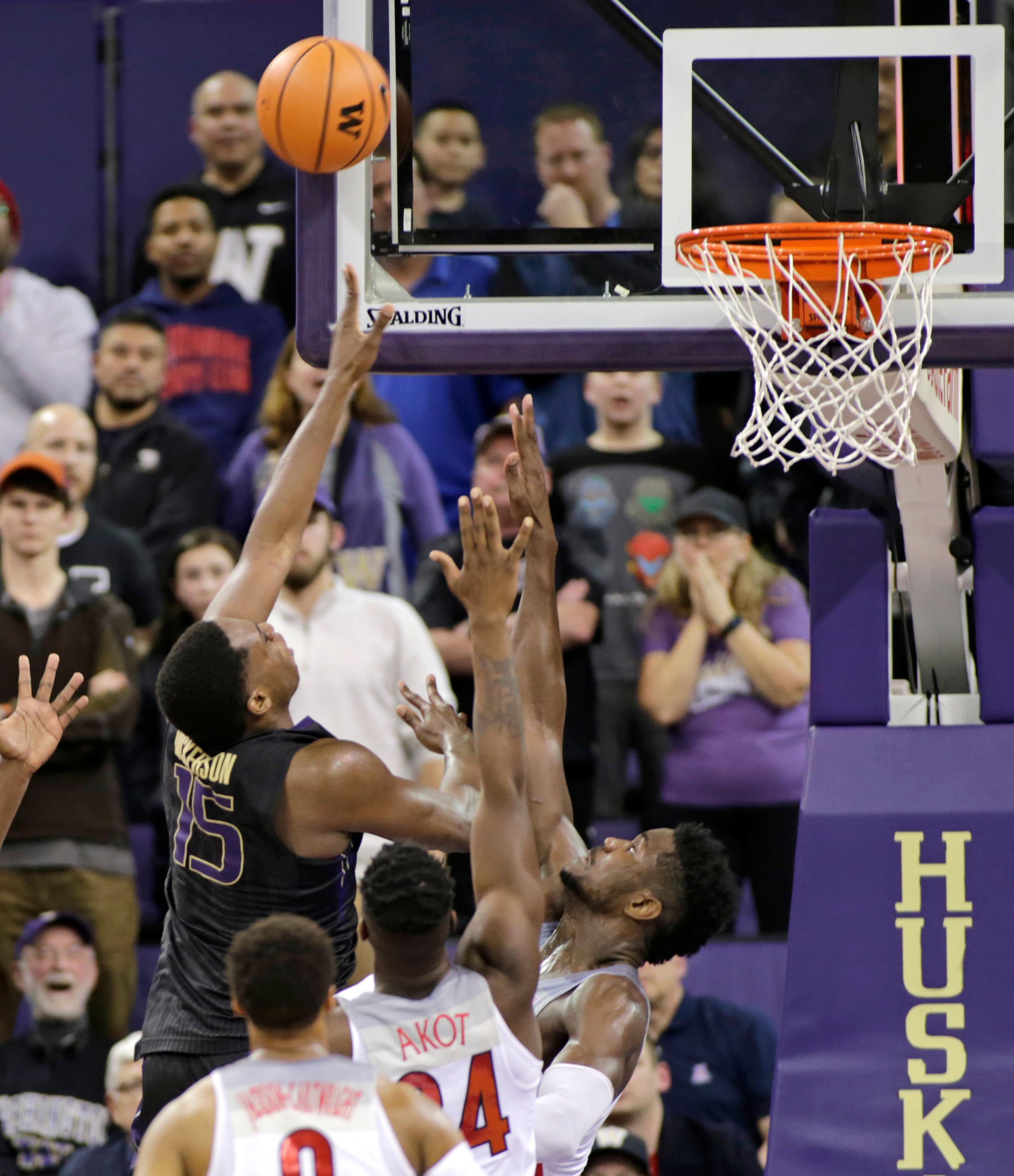 Washington's Noah Dickerson shoots over Arizona's Deandre Ayton, right, and Emmanuel Akot during the second half of an NCAA college basketball game Saturday, Feb. 3, 2018, in Seattle. Washington won 78-75 with Dickerson leading Washington with 25 points. (AP Photo/John Froschauer)