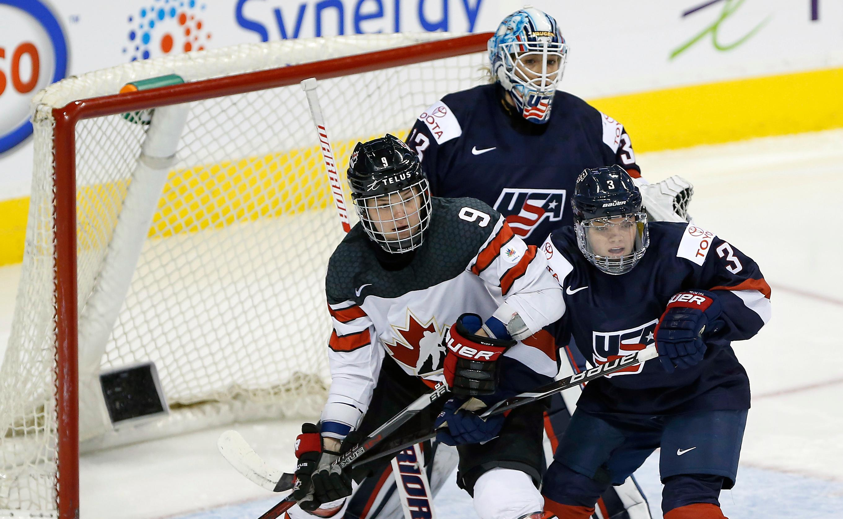 In this Tuesday, Dec. 5, 2017 photo, United States' Cayla Barnes (3) defends against Canada's Jennifer Wakefield (9) as USA's goaltender Alex Rigsby (33) keeps her eye on the puck during the third period of a women's hockey game in Winnipeg, Manitoba. Days after watching the U.S. women lose 5-1 to Canada in Boston on Oct. 25, Barnes learned she was moving from the bleachers to the bench as a call-up to the national team with the chance to earn a roster spot for the 2018 Winter Olympics. The defender, who turned 18 in January, quickly withdrew from college to become the U.S. team's youngest player chasing an opportunity that had seemed four years away. (John Woods/The Canadian Press via AP)