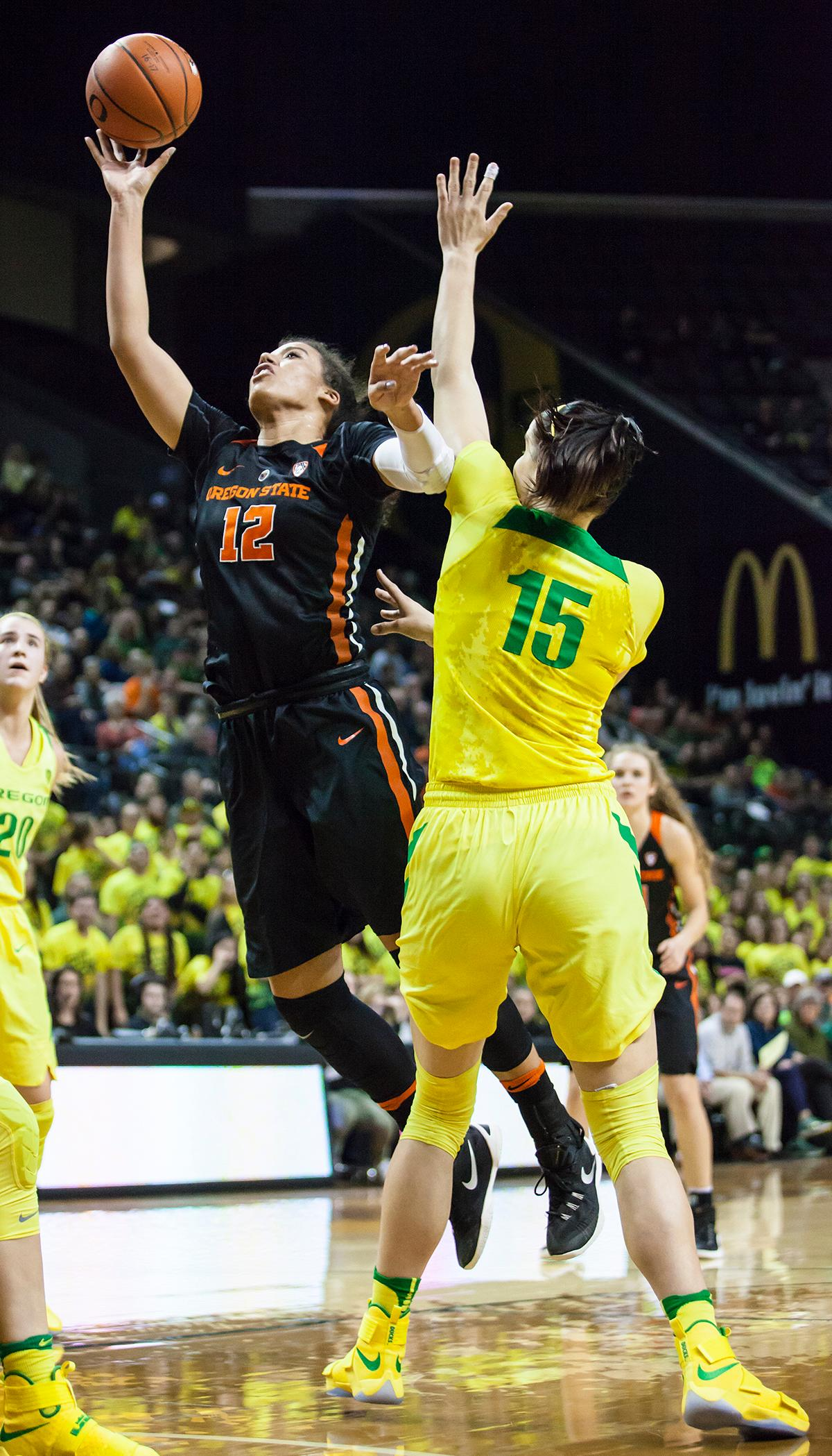 Oregon State forward Kolbie Orum (#12) breaks past Oregon forward Jacinta Vandenberg (#15) and leaps for a layup. Orum finished the night with 9 points and 4 rebounds. The Oregon Ducks lost 40 to 43 against the Oregon State Beavers after a tightly matched 4th quarter. Photo by Ben Lonergan, Oregon News Lab