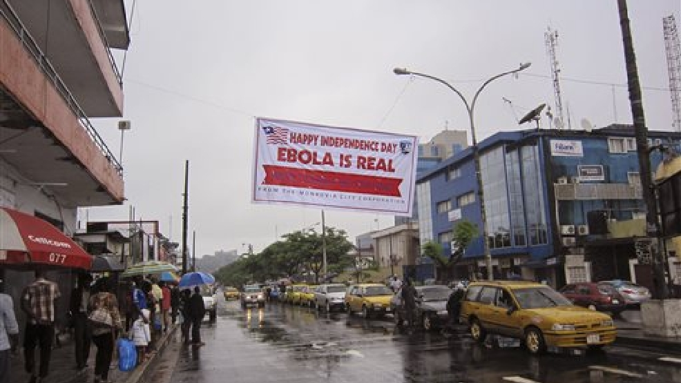 In this photo taken on Monday, July 28, 2014, people hang out in a street under a banner which warns people to be cautious about Ebola, in Monrovia, Liberia. Two American aid workers in Liberia have tested positive for the virus and are being treated there. U.S. health officials said Monday that the risk of the deadly germ spreading to the United States is remote. (AP Photo/Jonathan Paye-Layleh)