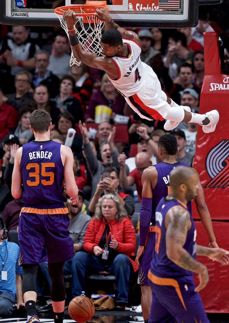 Portland Trail Blazers forward Maurice Harkless hands from the rim after a dunk against Phoenix Suns forward Dragan Bender during the second half of an NBA basketball game in Portland, Ore., Tuesday, Nov. 8, 2016. (AP Photo/Craig Mitchelldyer)