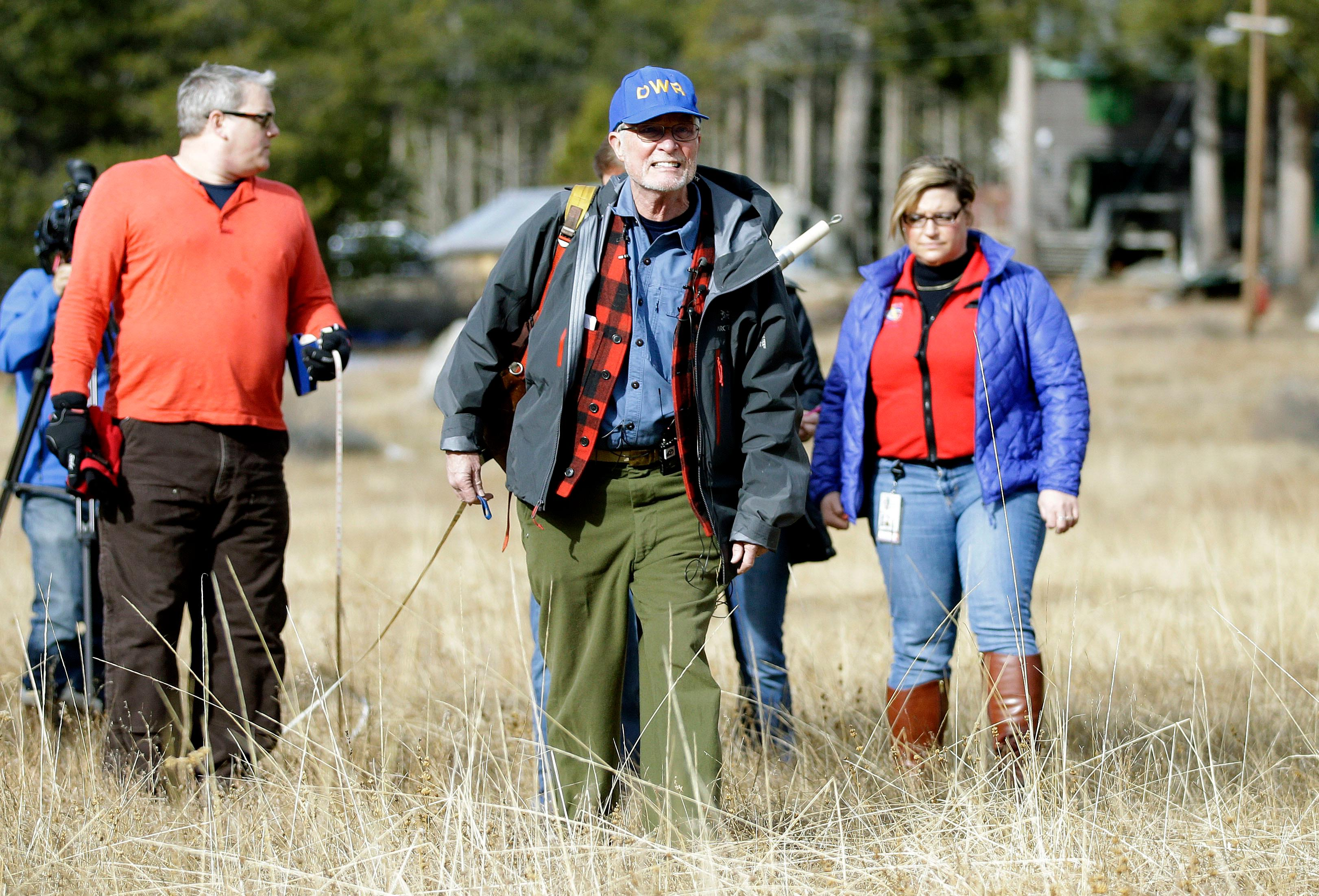 Frank Gehrke, center, chief of the California Cooperative Snow Surveys Program for the Department of Water Resources, crosses a nearly snow barren meadow while conducting the first snow survey of the season at the Phillips Station snow course, Wednesday, Jan. 3, 2018, near Echo Summit, Calif. The snow survey showed the snow pack at this location at 1.3 inches of depth with a water content of .4 inches. California's water managers are saying it's too early yet for fears that the state is sliding back into its historic five-year drought.  (AP Photo/Rich Pedroncelli)