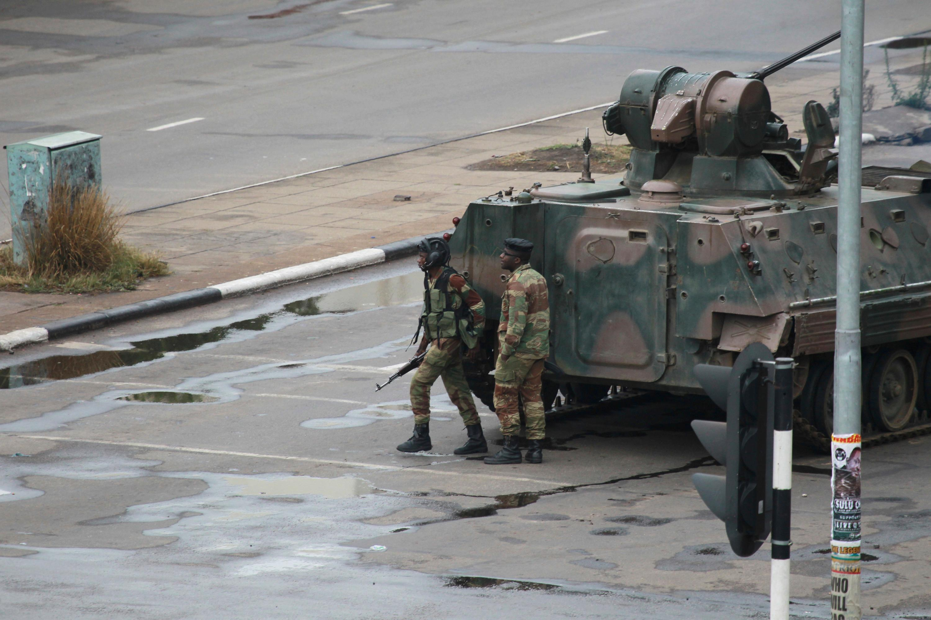 "A military tank is seen with armed soldiers on the road leading to President Robert Mugabe's office in Harare, Zimbabwe Wednesday, Nov. 15, 2017. Overnight, at least three explosions were heard in the capital, Harare, and military vehicles were seen in the streets. On Monday, the army commander had threatened to ""step in"" to calm political tensions over the 93-year-old Mugabe's possible successor. (AP Photo/Tsvangirayi Mukwazhi)"