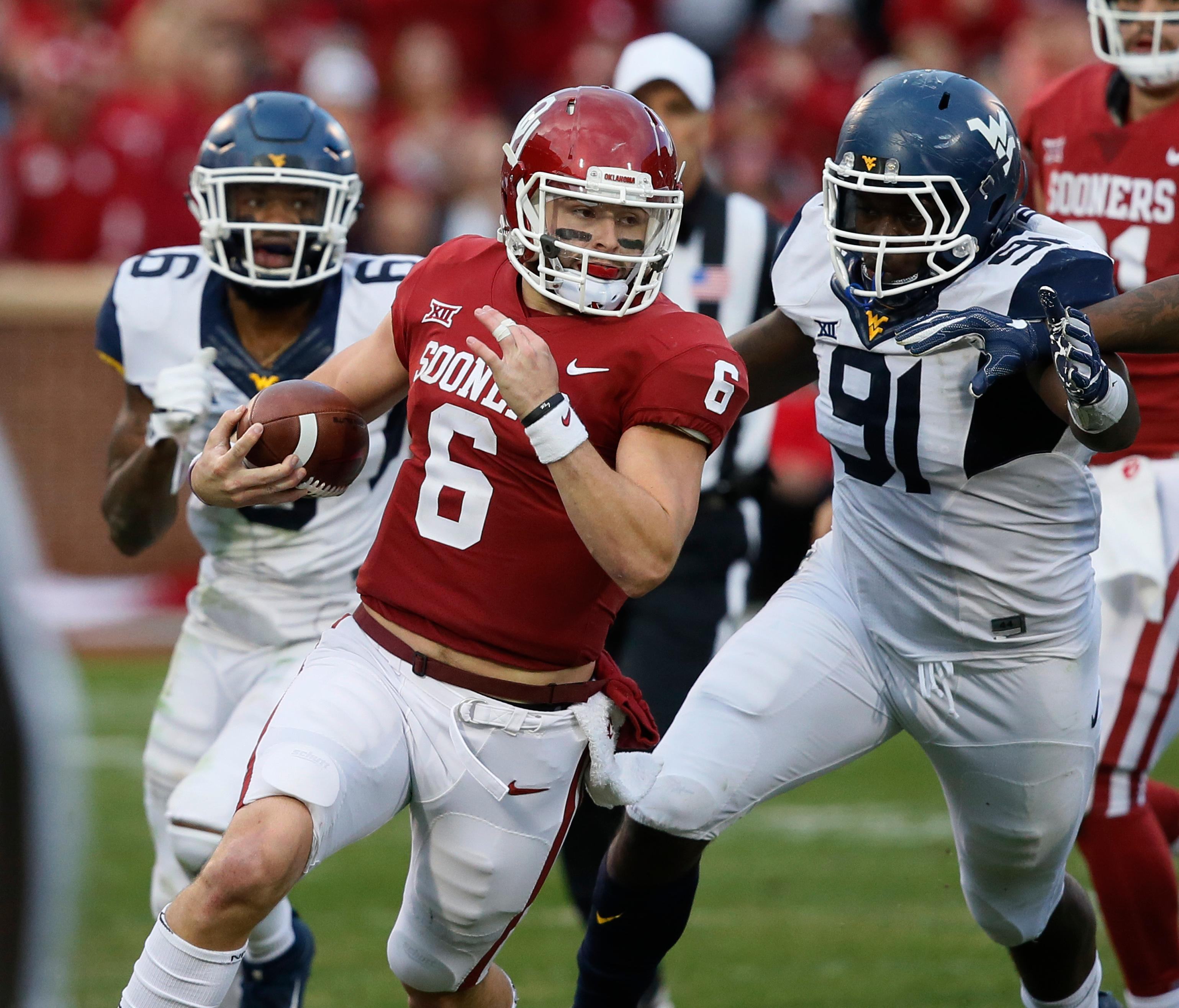 Oklahoma quarterback Baker Mayfield (6) carries past West Virginia safety Dravon Askew-Henry (6) and defensive lineman Ezekiel Rose (91) in the second quarter of an NCAA college football game in Norman, Okla., Saturday, Nov. 25, 2017. (AP Photo/Sue Ogrocki)