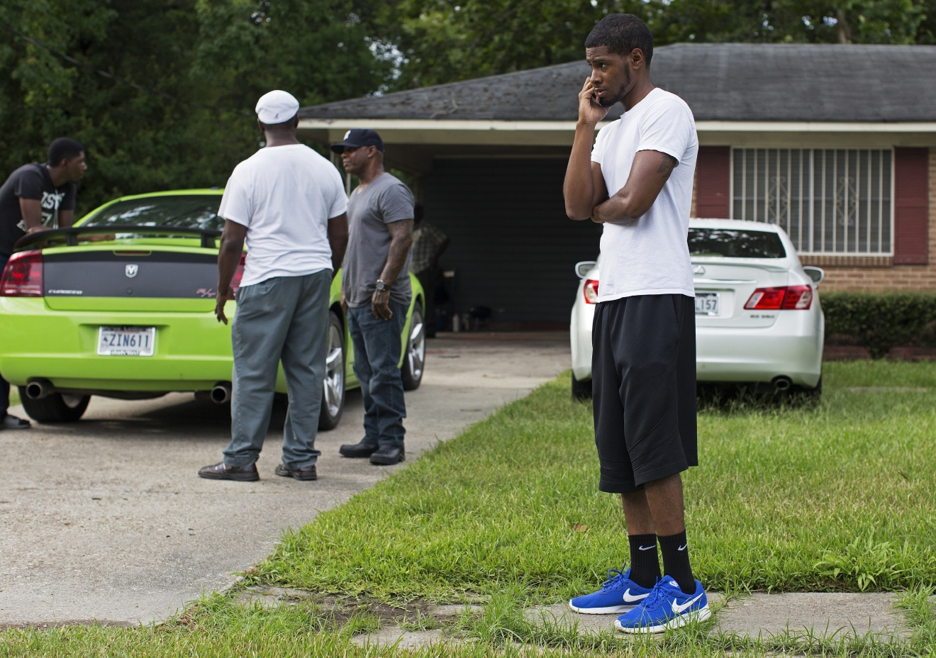 Kedrick Pitts, the half-brother of slain Baton Rouge Policeman, Cpl. Montrell Jackson, talks on the phone in front of Montrell's mother's house in Baton Rouge, La., Sunday, July 17, 2016. Jackson was one of the law enforcement officers who were shot and killed on Sunday morning. (AP Photo/Max Becherer)