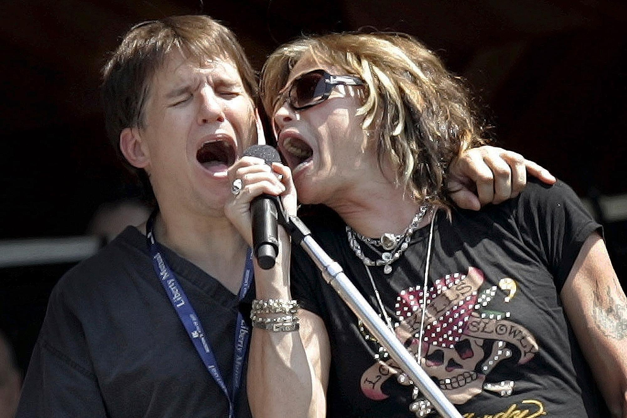 FILE - In this July 3, 2006 file photo, Boston Pops conductor Keith Lockhart, left, and Aerosmith's lead singer Steven Tyler sing together during a sound-check and rehearsal for the Fourth of July show at the Hatch Shell in Boston. Lockhart marks 25 years with the Boston Pops in 2020, making him the orchestra's second longest-tenured conductor after Arthur Fiedler. (AP Photo/Chitose Suzuki, File)