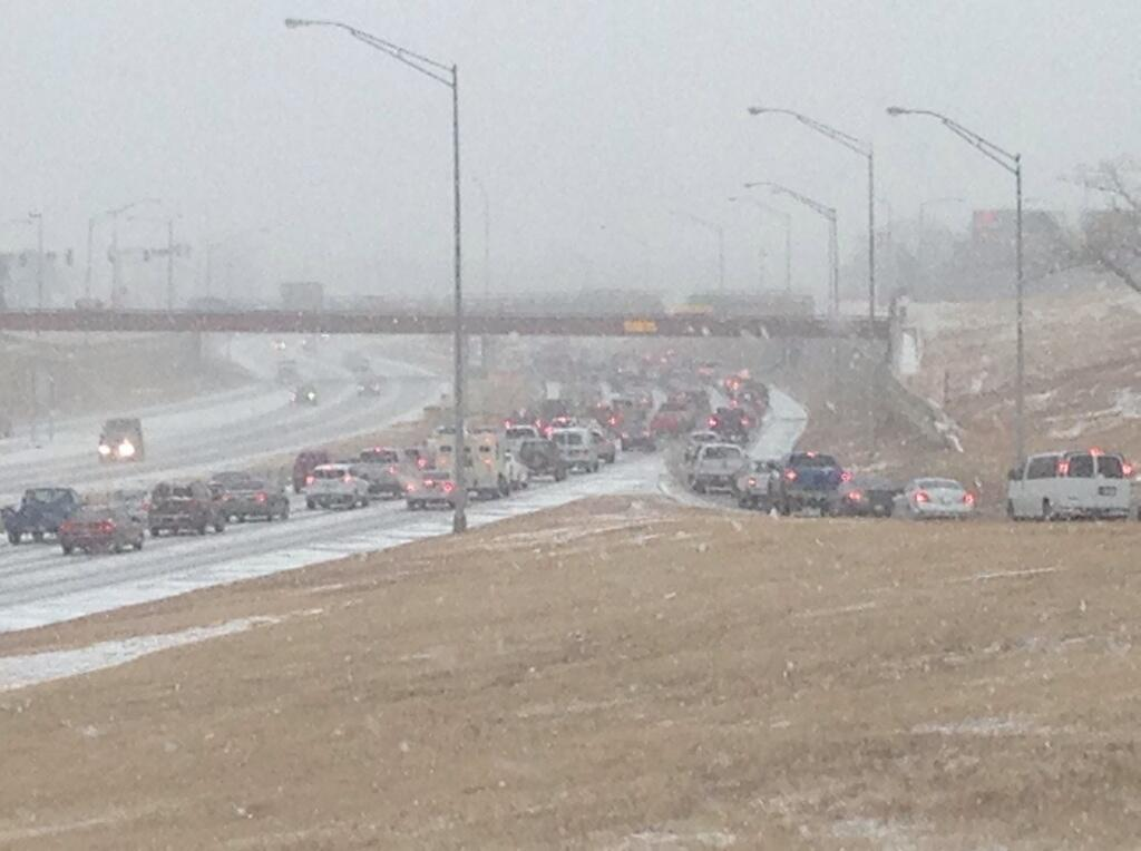 Traffic at NW Expressway and Hefner backs up as the snow falls Thursday