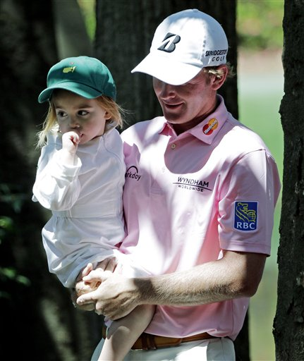 Brandt Snedeker carries his daughter Lily during the par three competition at the Masters golf tournament Wednesday, April 9, 2014, in Augusta, Ga.