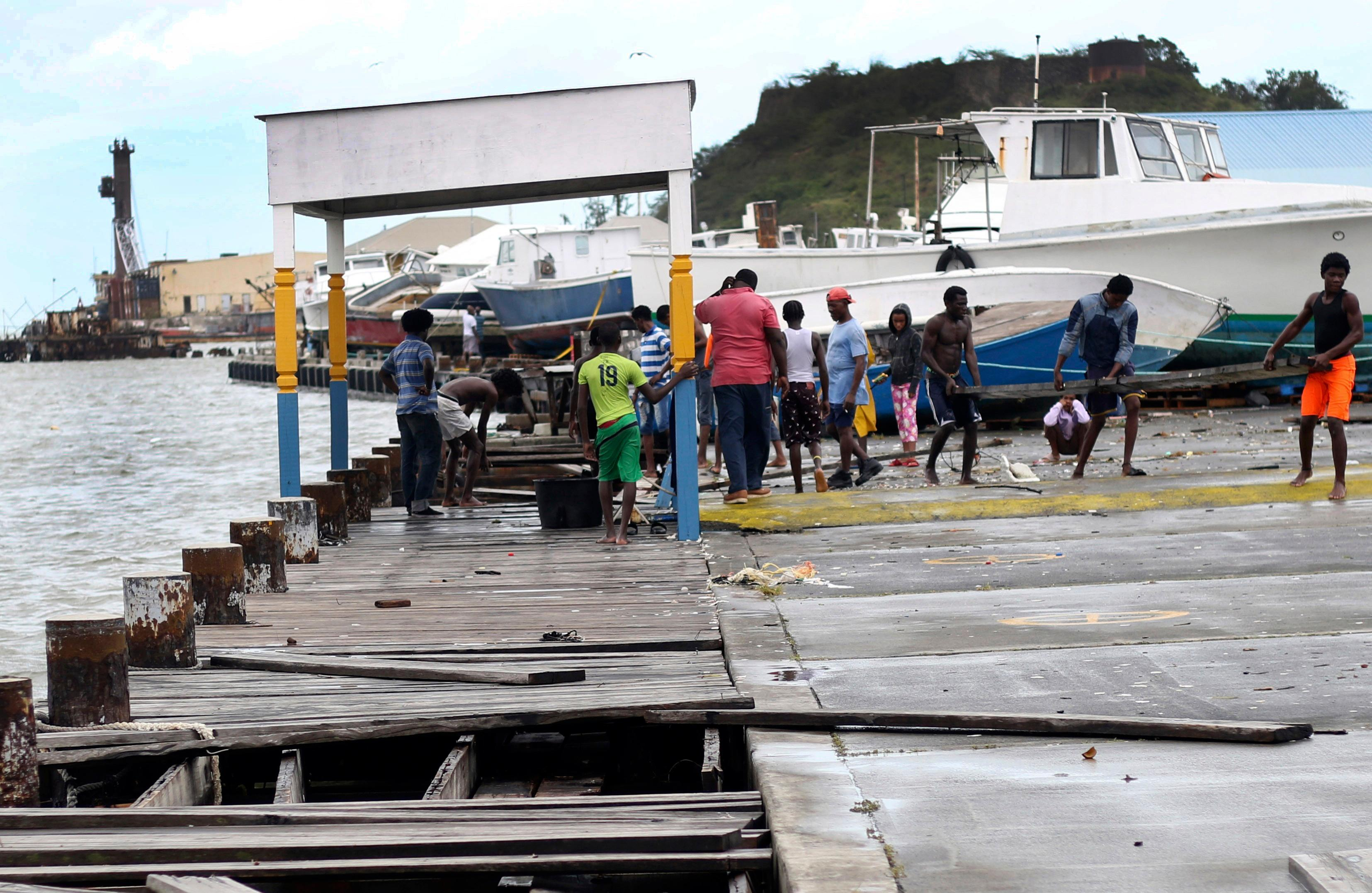 People recover broken parts of the dock after the passing of Hurricane Irma, in St. John's, Antigua and Barbuda, Wednesday, Sept. 6, 2017. Heavy rain and 185-mph winds lashed the Virgin Islands and Puerto Rico's northeast coast as Irma, the strongest Atlantic Ocean hurricane ever measured, roared through Caribbean islands on its way to a possible hit on South Florida. (AP Photo/Johnny Jno-Baptiste)