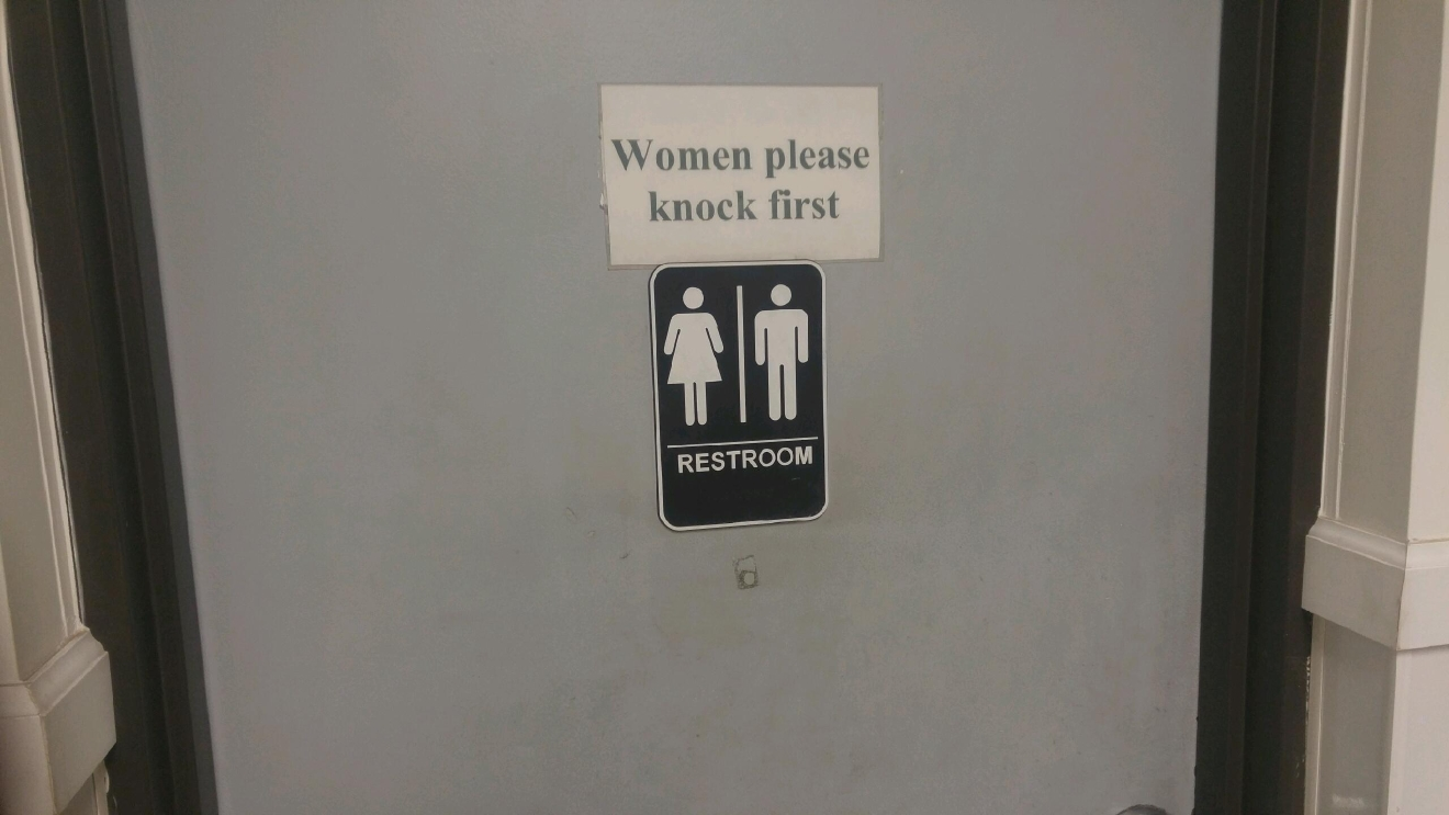 "A female employee  filed a complaint of gender discrimination. She didn't have access to a women's bathroom. This unisex bathroom sign was later added as was a note telling ""women to please knock."""
