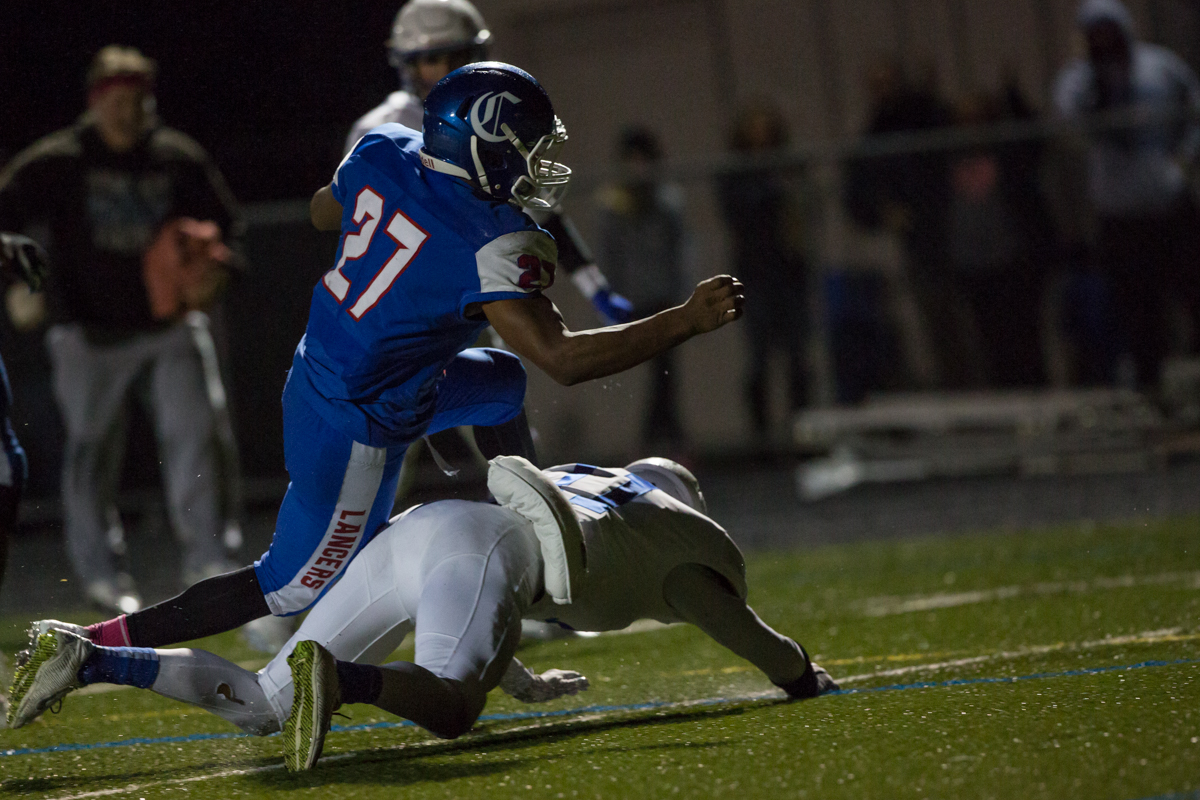 Churchill Lancers running back Sam Jackson (#27) leaps over an Eagle Point defender for a touchdown. Eagle Point defeated Churchill 42-37.  Photo by Austin Hicks, Oregon News Lab