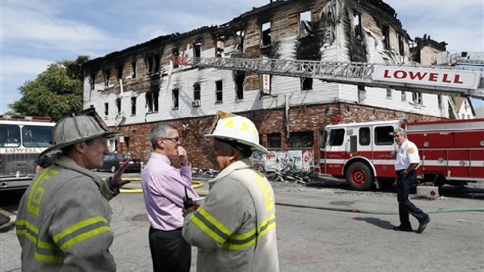 Fire officials observe the scene of a burned three-story apartment and business building in Lowell, Mass., Thursday, July 10, 2014, where officials said seven people died in a fast-moving pre-dawn fire. All seven victims were found in third-floor units of the three-story building that had businesses on the ground floor and apartments on the upper floors, fire officials said. (AP Photo/Elise Amendola)
