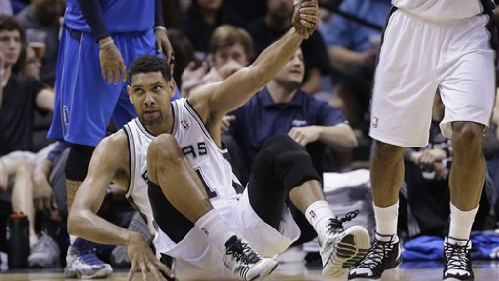 San Antonio Spurs' Tim Duncan (21) is helped off the floor after he was fouled during the second half of Game 1 of the opening-round NBA basketball playoff series against the Dallas Mavericks, Sunday, April 20, 2014, in San Antonio. San Antonio won 90-85. (AP Photo/Eric Gay)